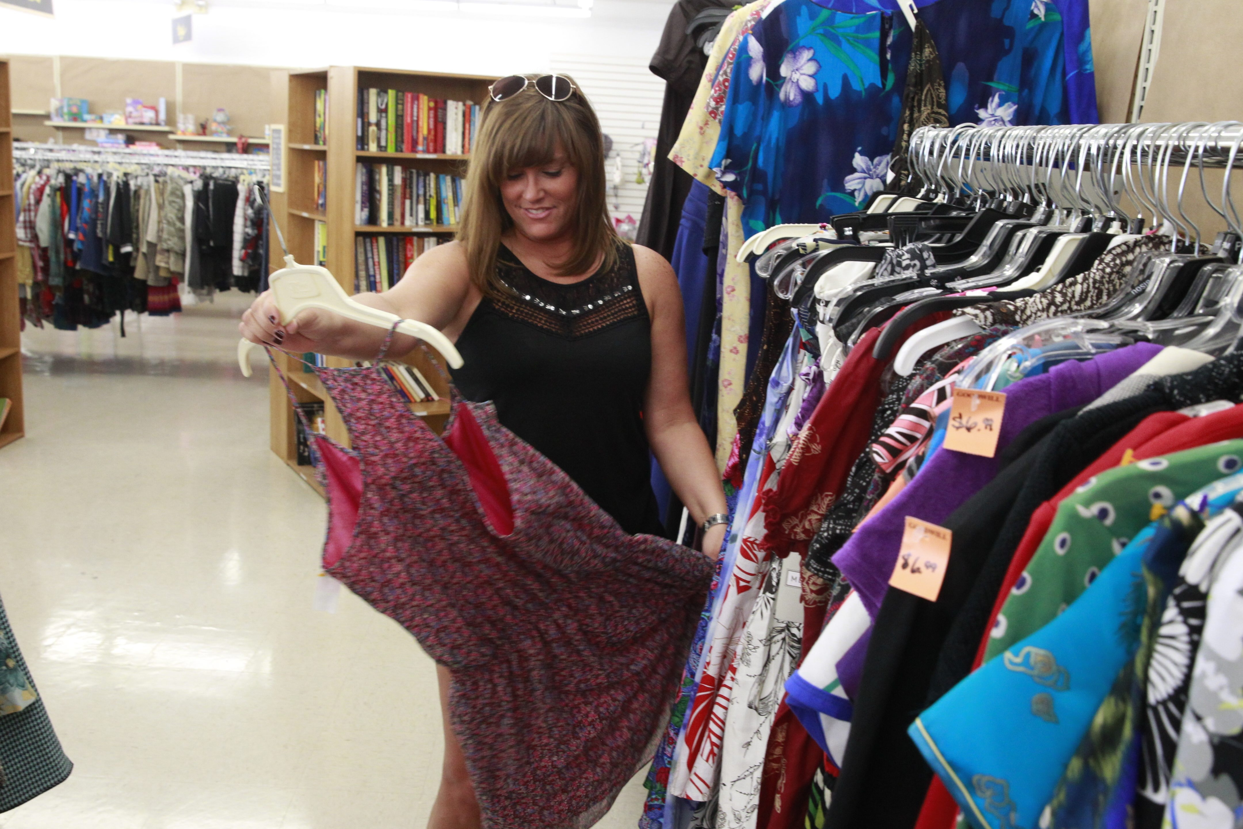 Heather Eminger looks at a dress as she shops at Goodwill which re-opened its newly remodeled Tonawanda store, which reflects a broader effort by thrift stores to engage new customers by offering a better shopping experience in Town of Tonawanda. (John Hickey/Buffalo News)