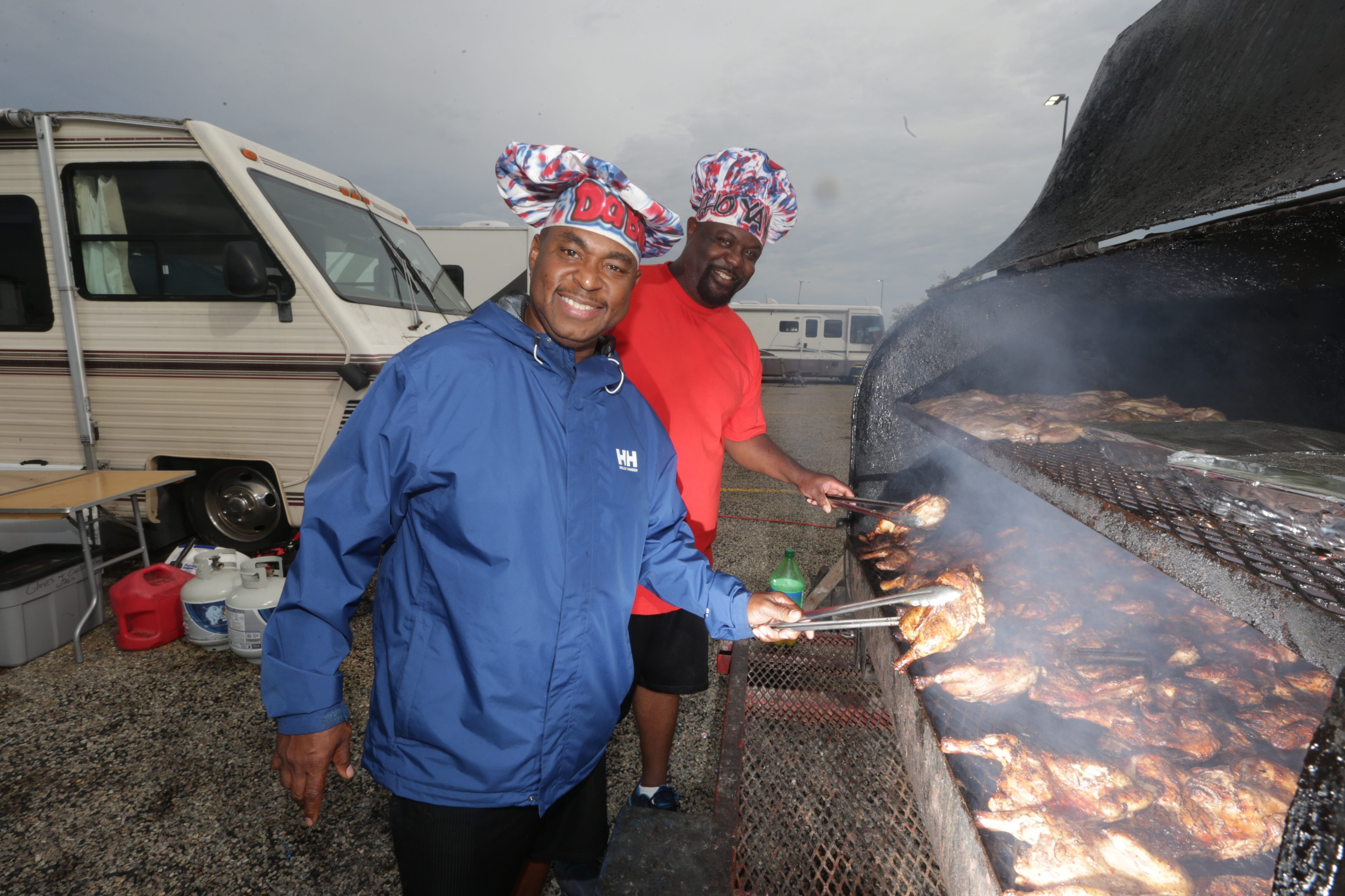 Bills game regulars Derrick Norman, left, and Richard Peter-son grill chicken in Ralph Wilson Stadium RV Lot on Saturday.