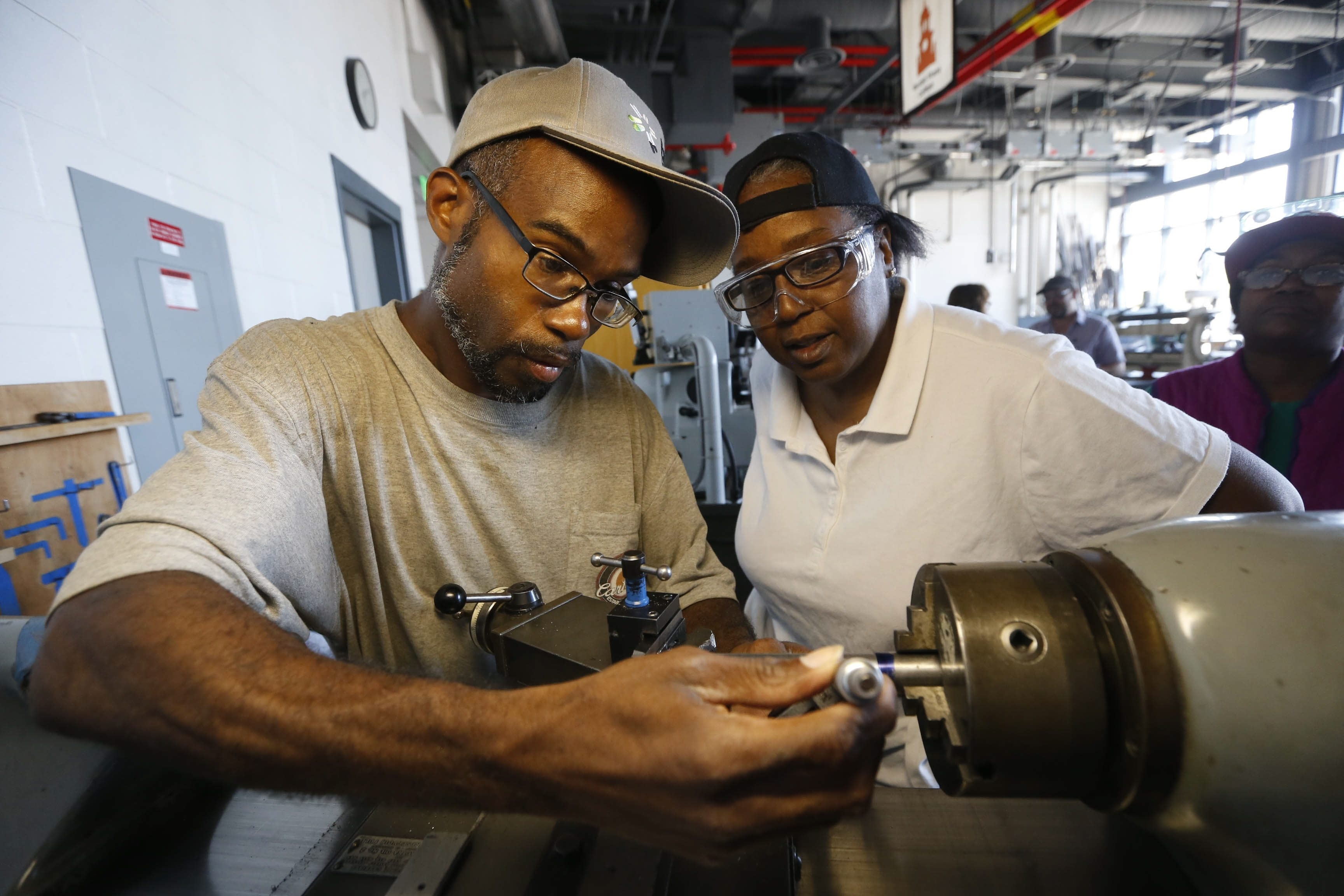 Eric Artis, left, and classmate Ruby Laster, both of Buffalo, work on a metal lathe machine at the Advanced Manufacturing Training Program at SUNY Buffalo State. The program is one of several in the region training people to replace retiring factory workers.