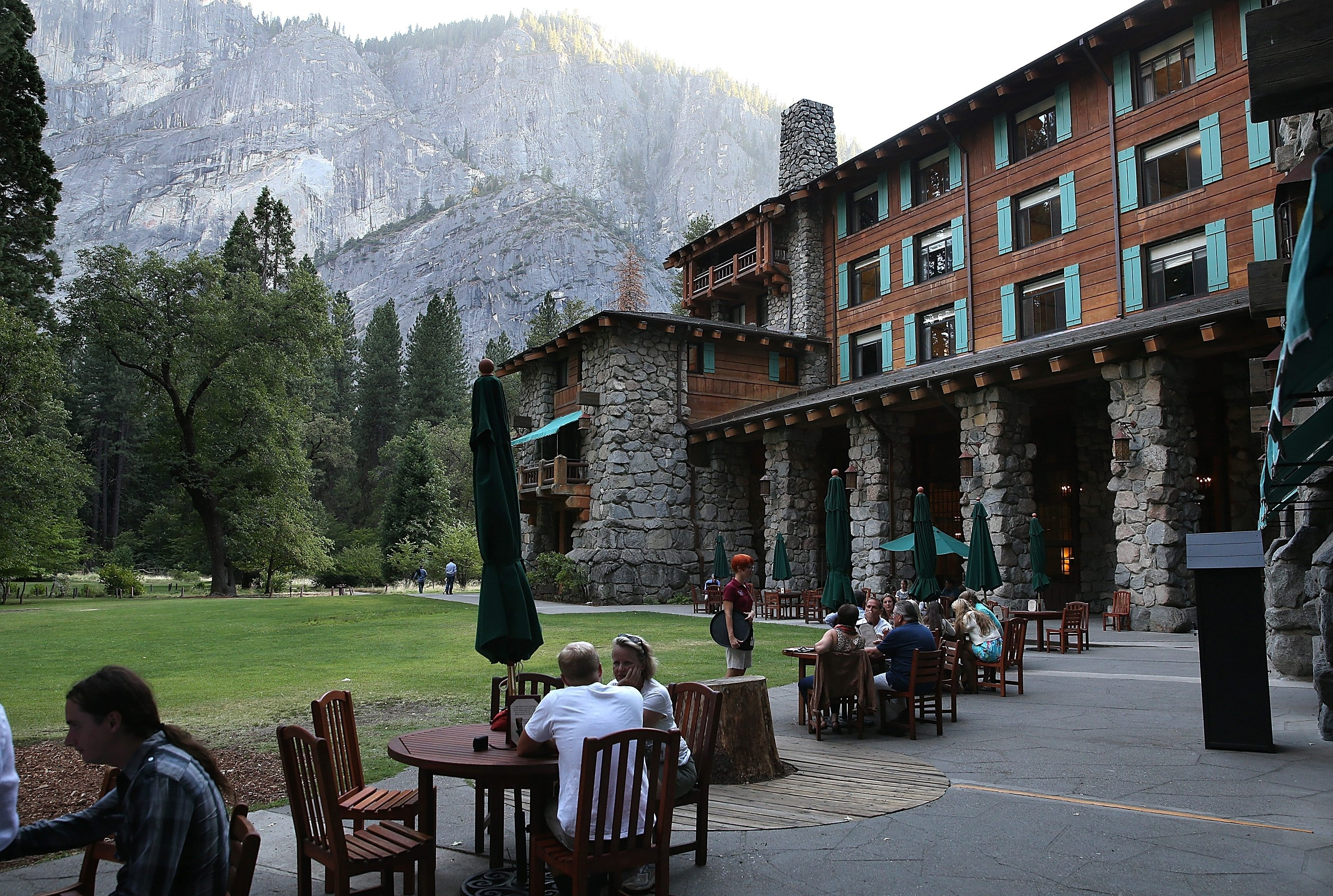 Park visitors sit outside the Ahwahnee Hotel in Yosemite National Park. Delaware North is suing the National Park Service over the value of the names of several park facilities, which the Buffalo-based company operated for many years. (Getty  Images)
