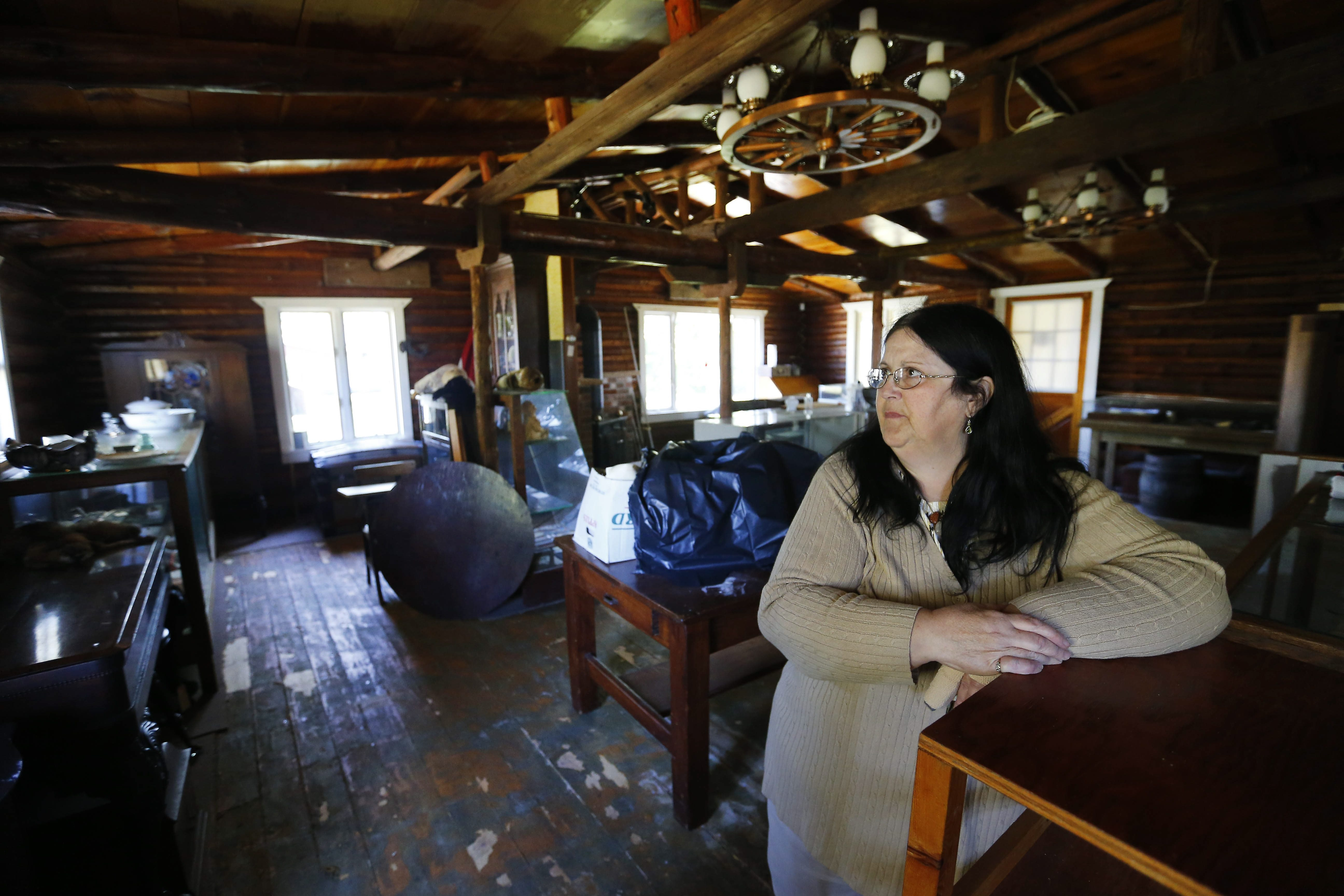 Rose Schaeffer, president of the Newfane Historical Society, looks at some of the water damage that occurred in the group's log cabin over the winter.