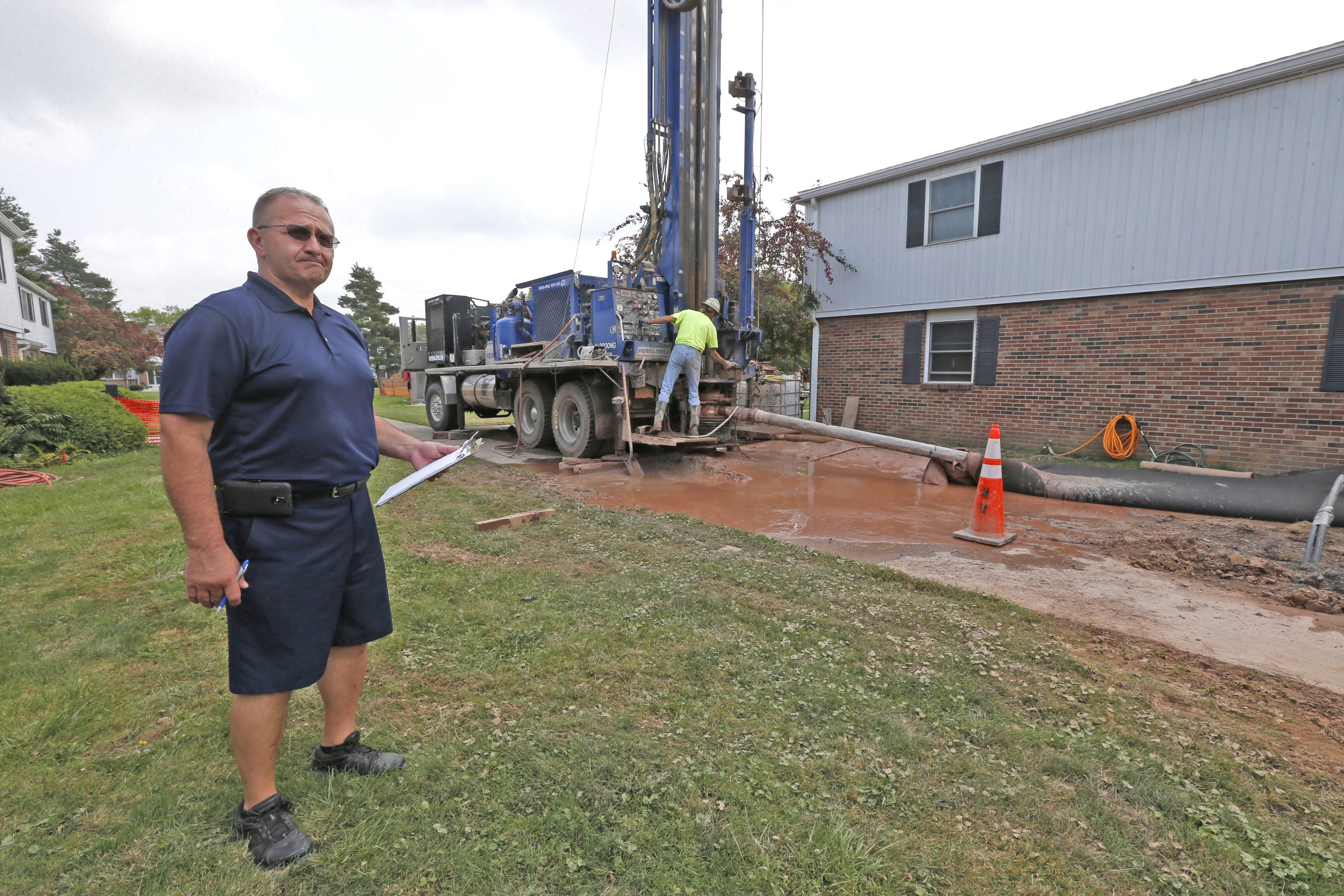 Lockport Housing Authority modernization coordinator Jeff Haag, left, monitors the progress as Kevin Bush of Nothnagle Drilling, Henrietta, works on the early phases of a geothermal heating and cooling system at Autumn Gardens.