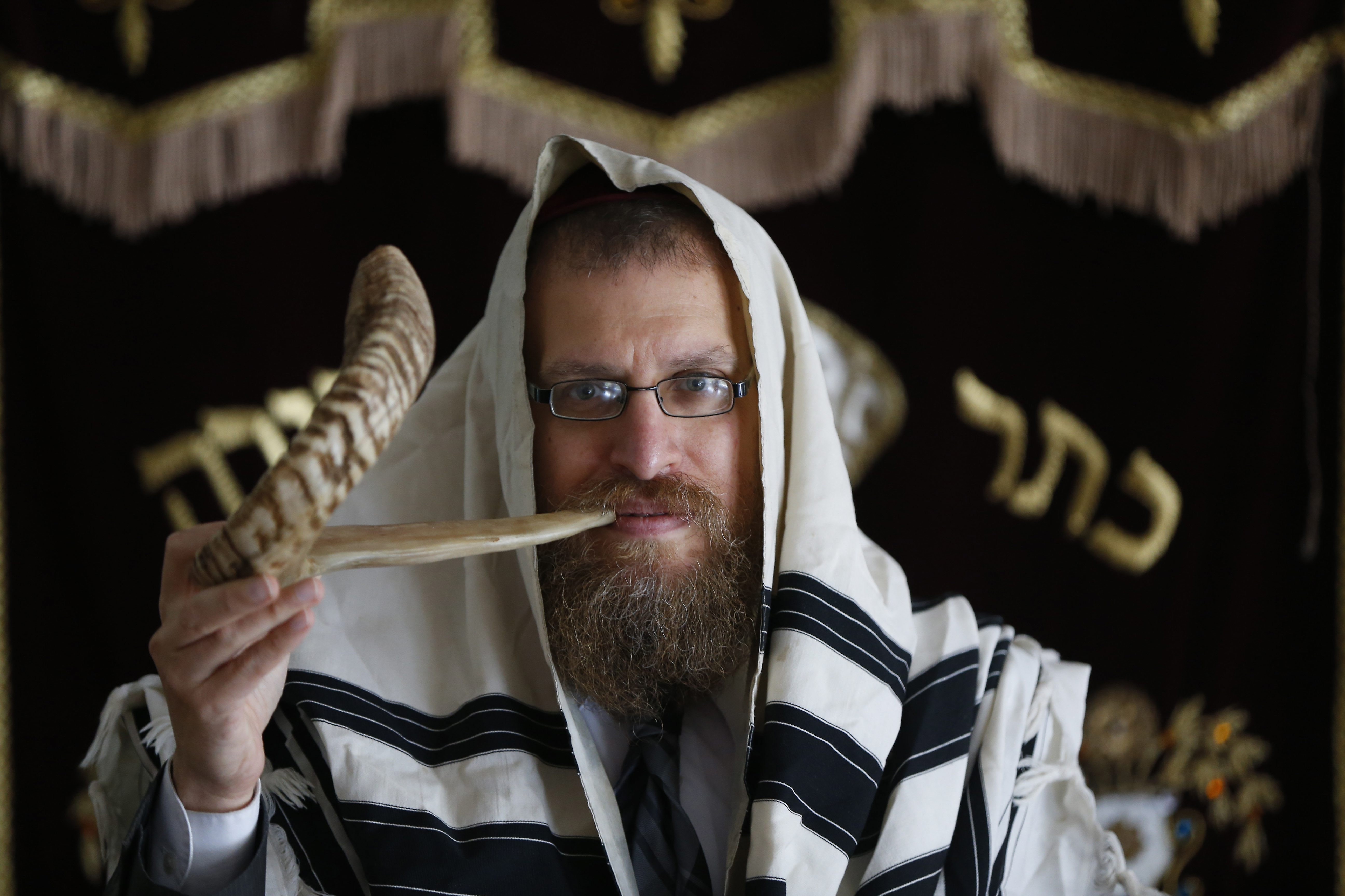 Rabbi Laizer Labkovski blows the shofar at the Jewish Discovery Center in Amherst. Labkovski, who with his wife, Chani, has 10 children and an 11th on the way, says he knew from an early age that he wanted to be involved in community work.