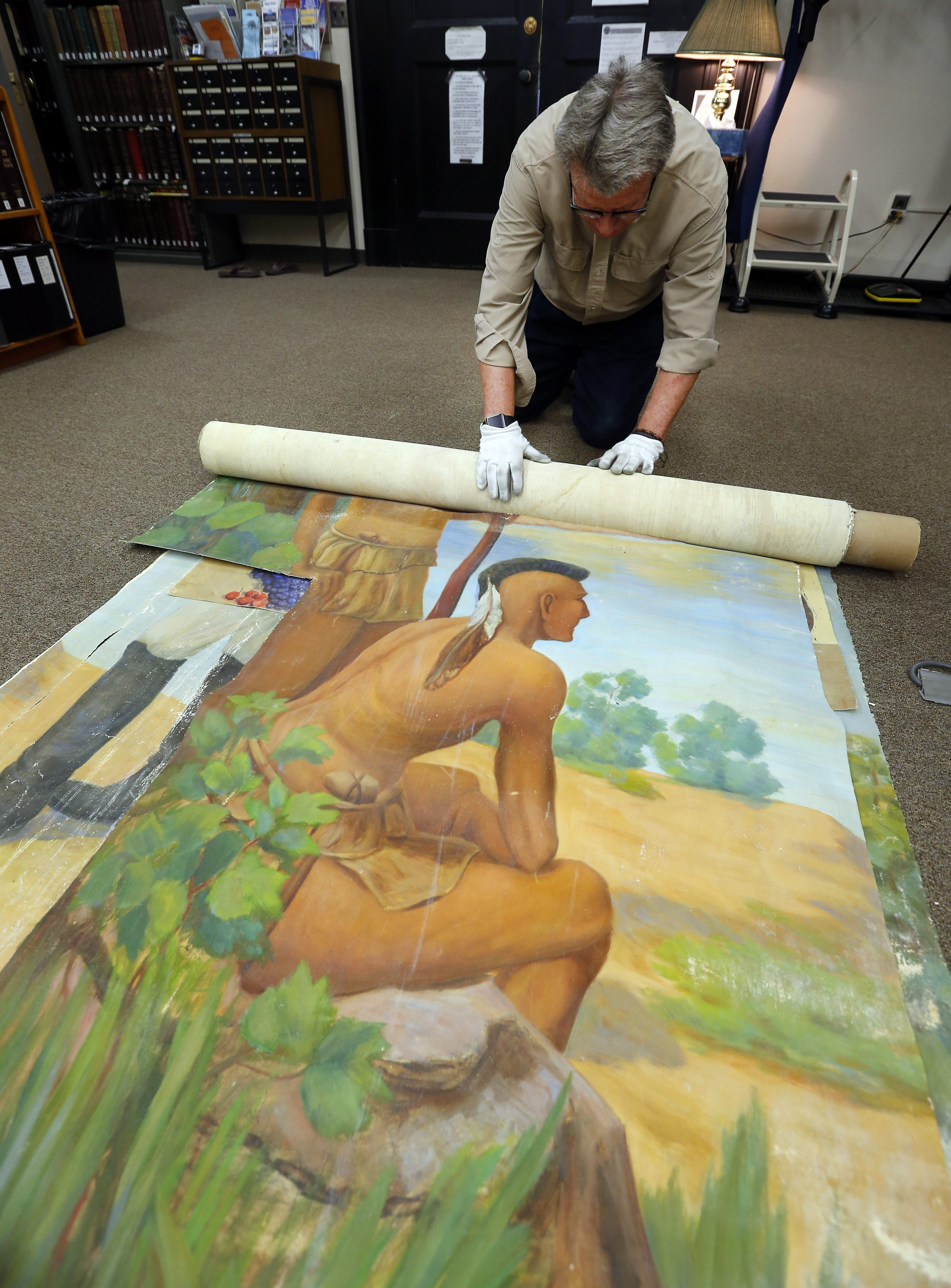Niagara County Deputy Historian Ron Cary rolls out pieces of murals that were painted by Emil Strub and discovered during a renovation of the Mount View Assisted Living Facility in Lockport.