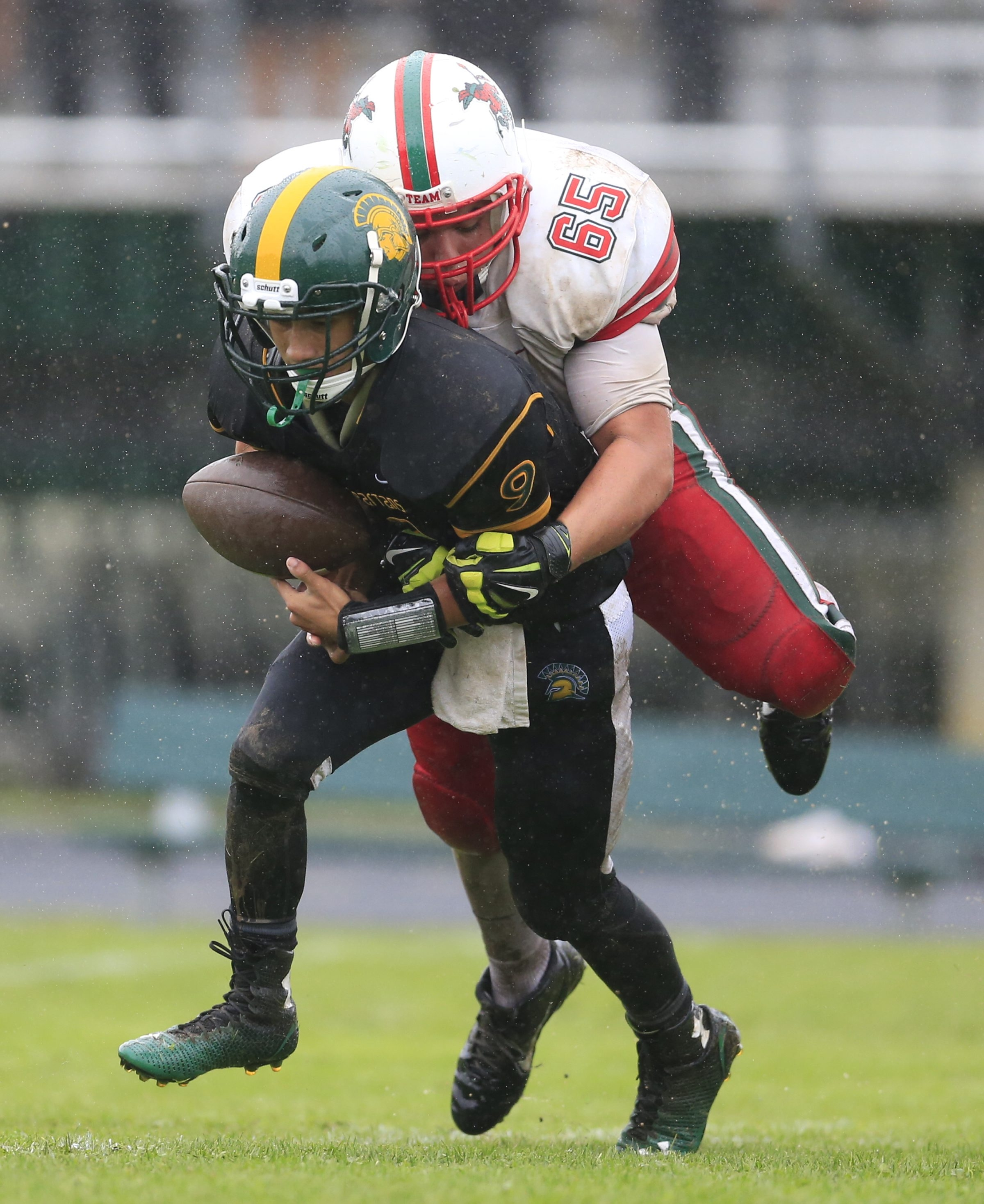Williamsville North quarterback Jose Padilla is sacked by Jamestown's Jeremy Bush during the Red Raiders' victory in the rain Saturday.