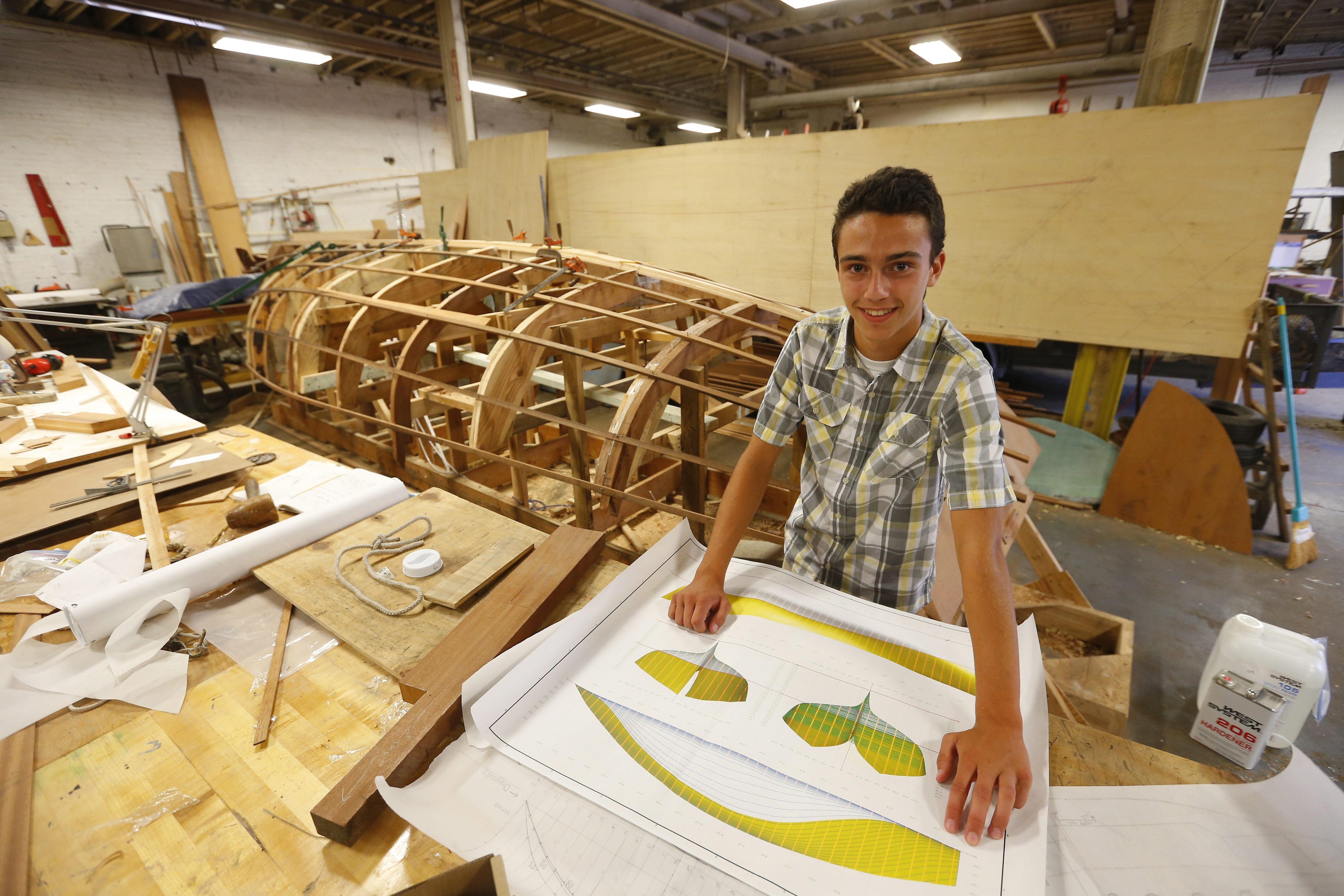 """Owen Mylotte stands with some of the plans he has for the ship he wants to build at the Buffalo Maritime Center.  """"The feeling of sailing got to me,"""" said Owen, who fell in love with sailboats after riding on the Spirit of Buffalo."""