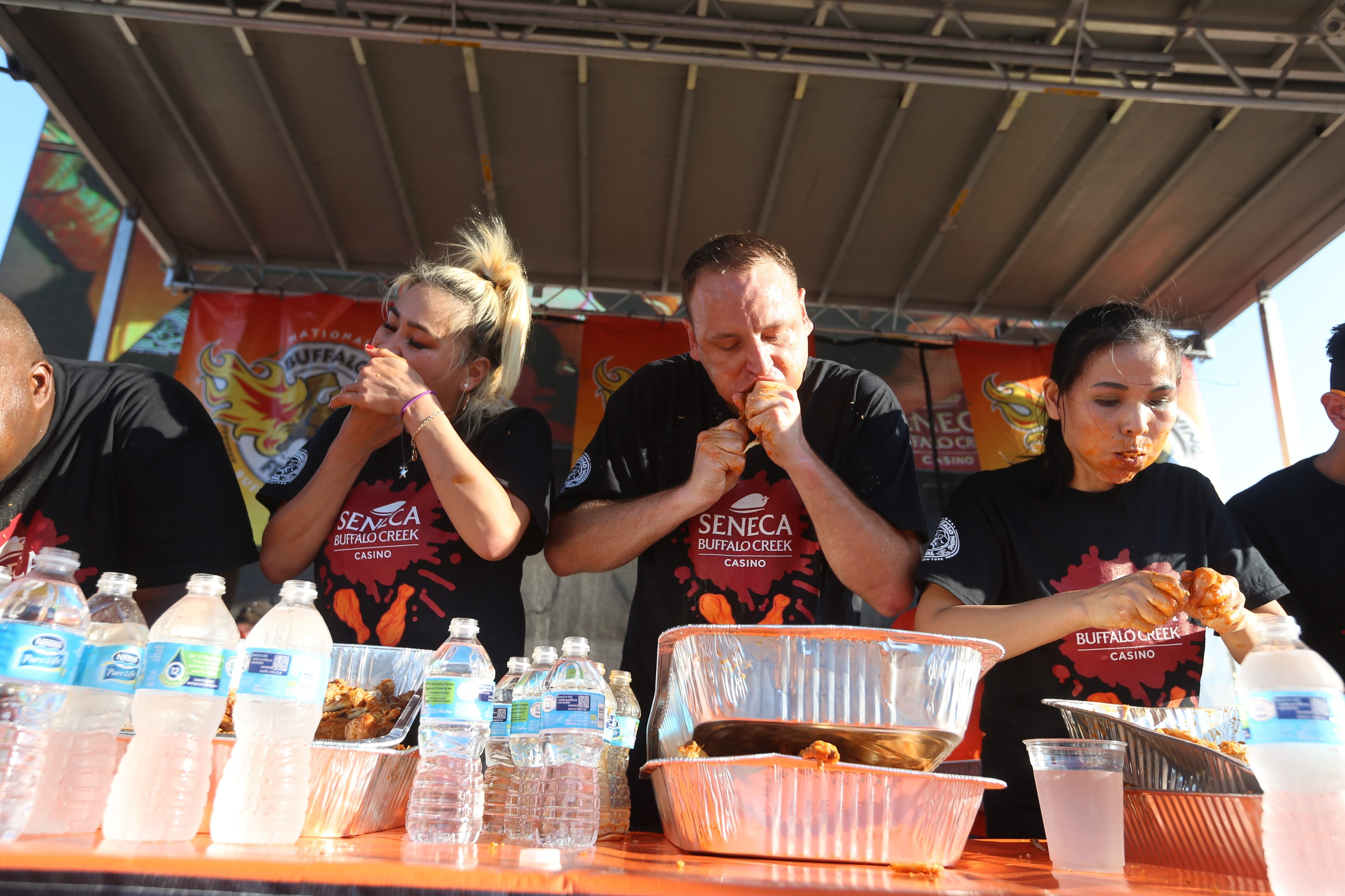 """Miki Sudo, left, ate 170 wings to take second place, Joey """"Jaws"""" Chestnut consumed 205 to take first place, and Sonya """"The Black Widow"""" Thomas ate 157 wings to place third in the U.S. Chicken Wing Eating Championship at Coca-Cola Field on Sunday."""