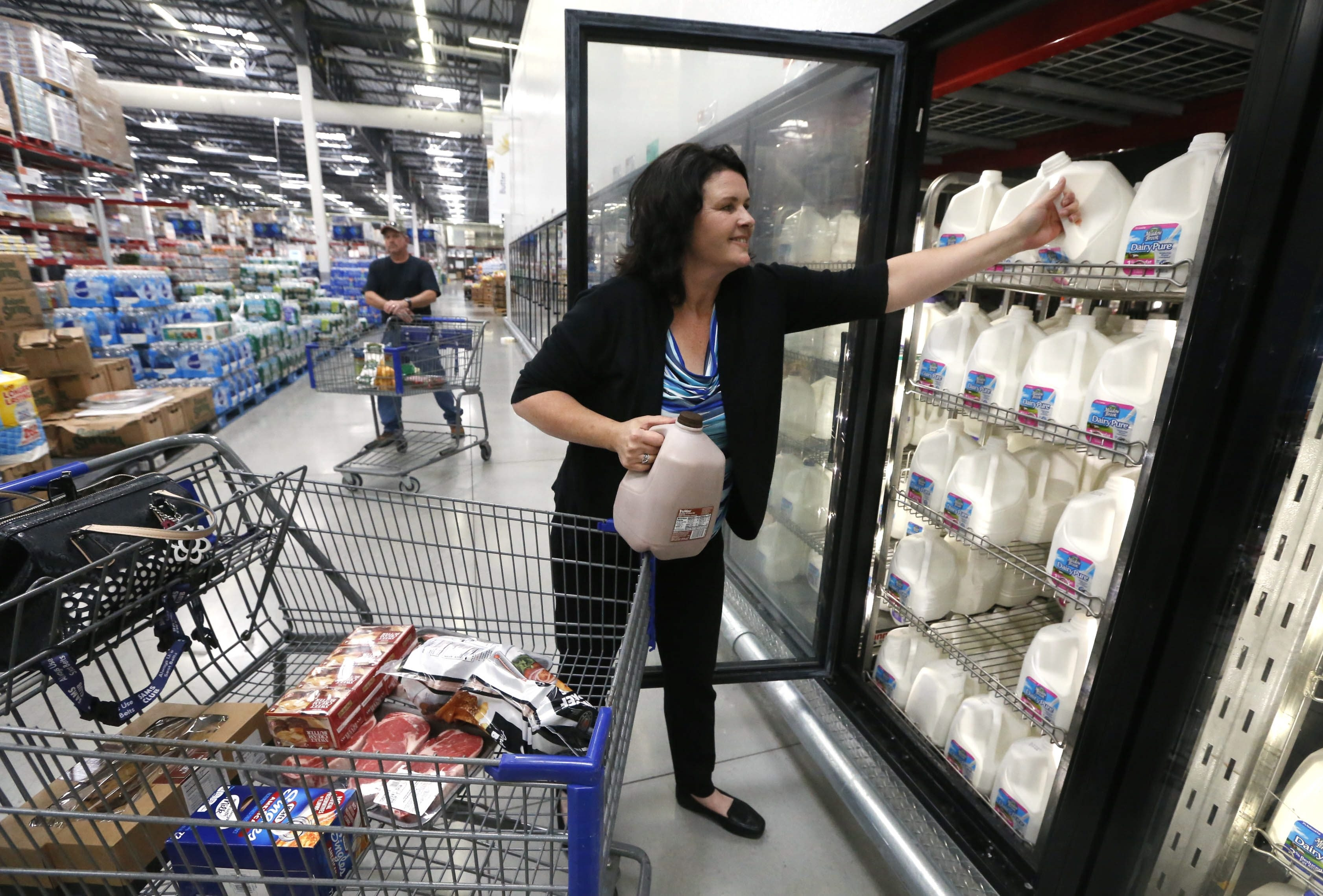 """Lisa Aulbrook of Niagara Falls, Ont., shops for groceries at Sam's Club in Niagara Falls, N.Y. Canadian shoppers find they can save significantly on their monthly grocery bills by making a short trek across the border to shop in U.S. supermarkets.   """"This would cost $75 at home. It's like a rich man's food over there."""" Lisa Aulbrook, refering to a giant pork loin priced at $19.48"""