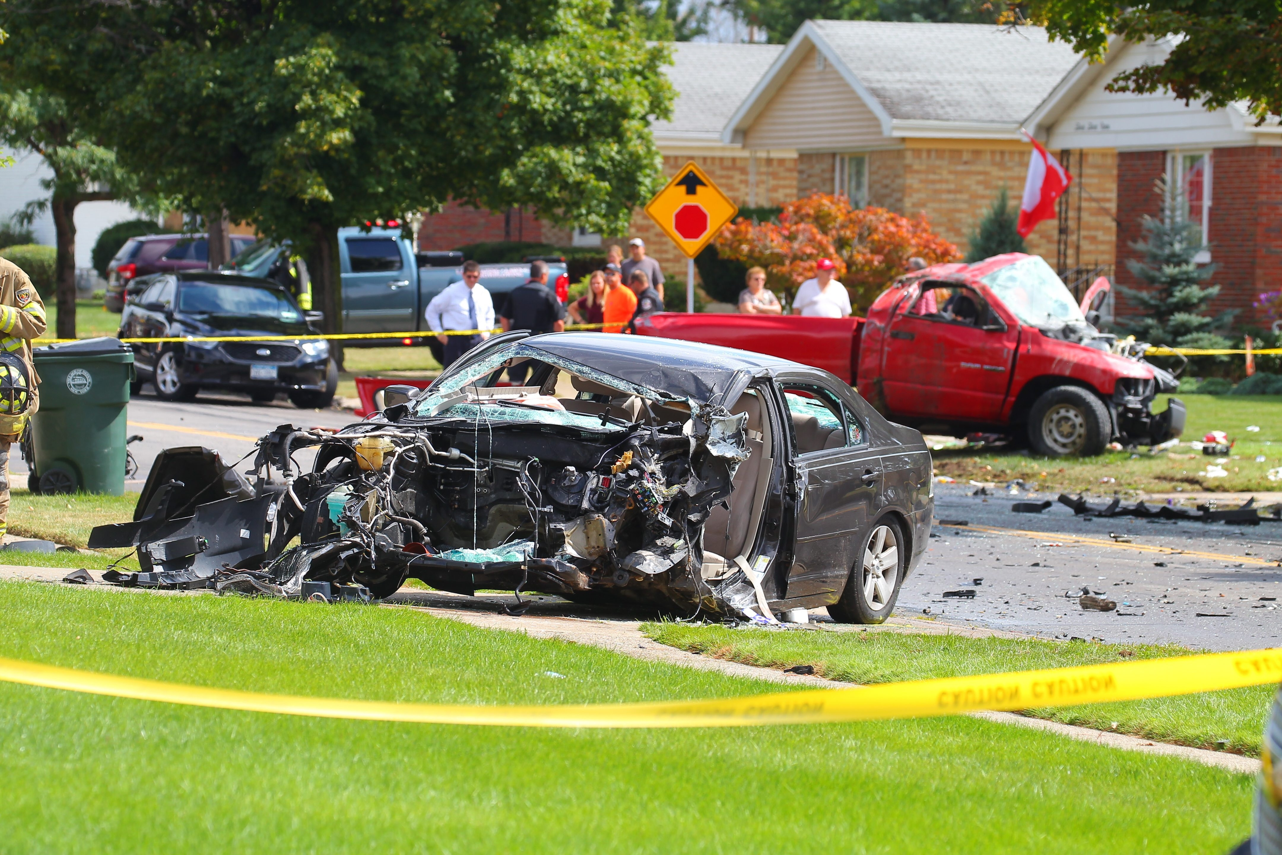 The wreckage of a sedan sits on a lawn after it collided with a pickup truck in Depew Wednesday.