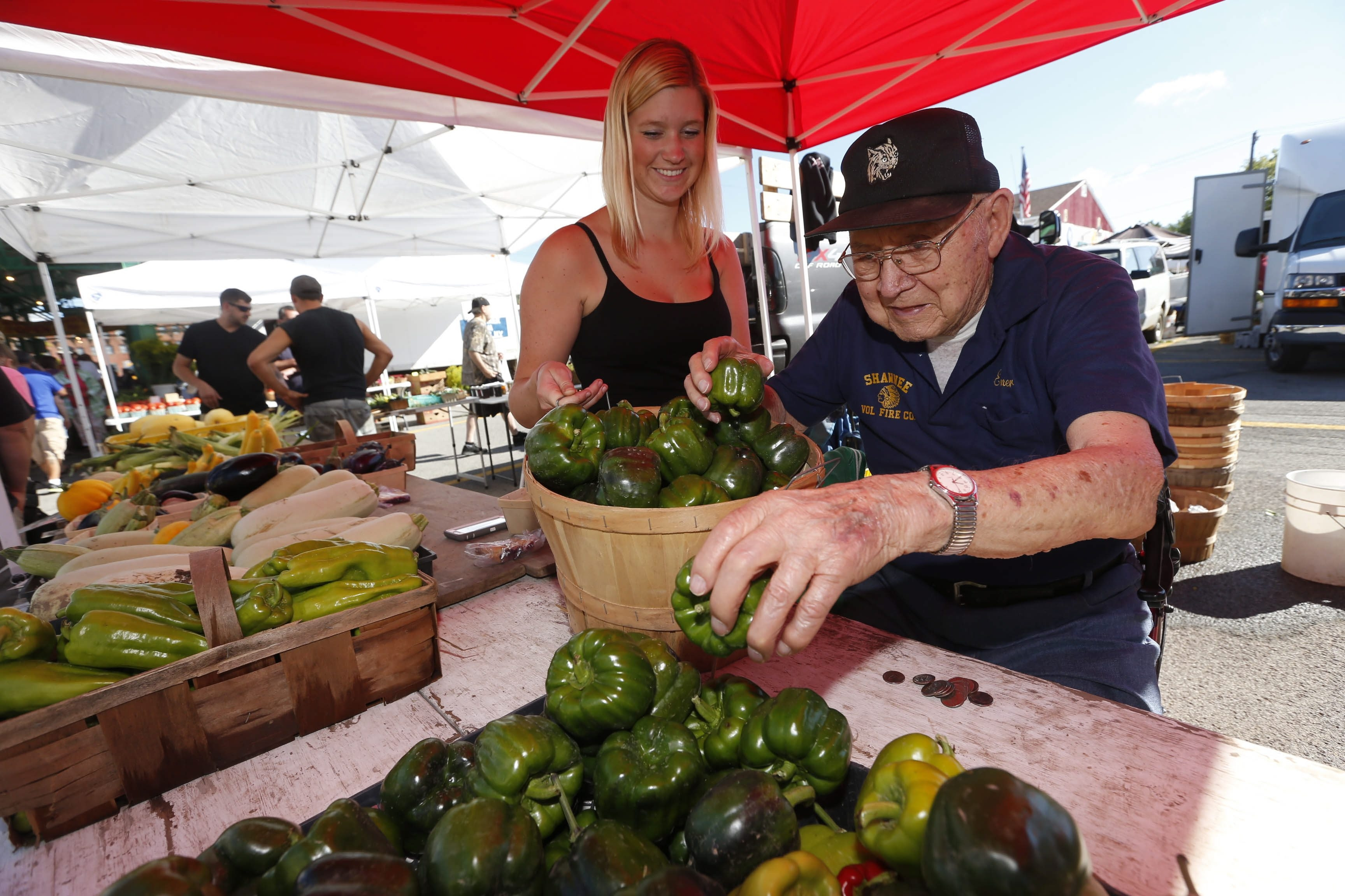 Elmer Moje, 102, and his granddaughter Carly A. Fabiny place peppers on a table at their stand at the North Tonawanda Market at Robinson and Payne.