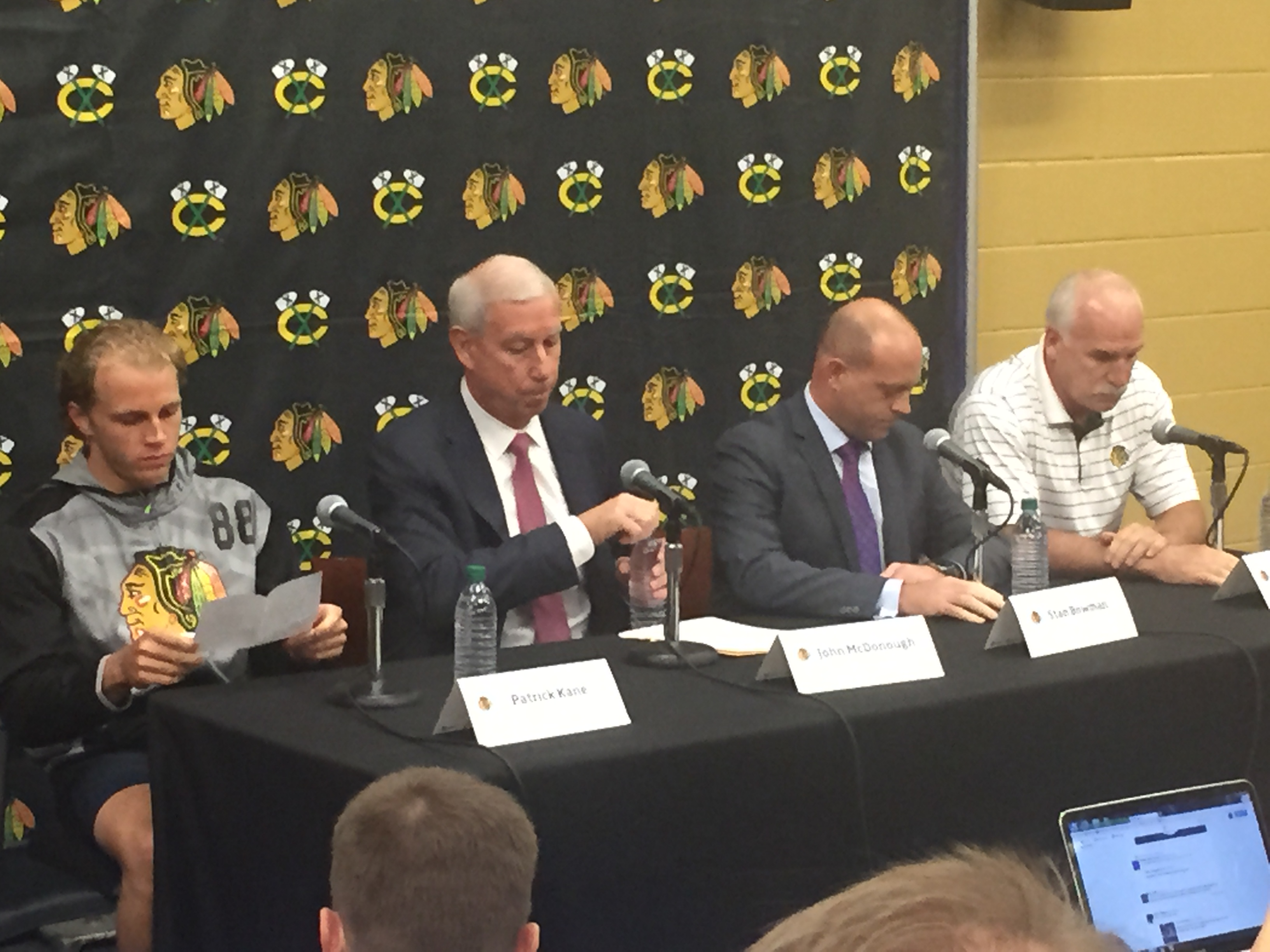Patrick Kane reviews his statement as Hawks president John McDonough, GM Stan Bowman and coach Joel Quenneville ponder their thoughts prior to the start of Thursday's press conference in South Bend, Ind. (Mike Harrington/Buffalo News).