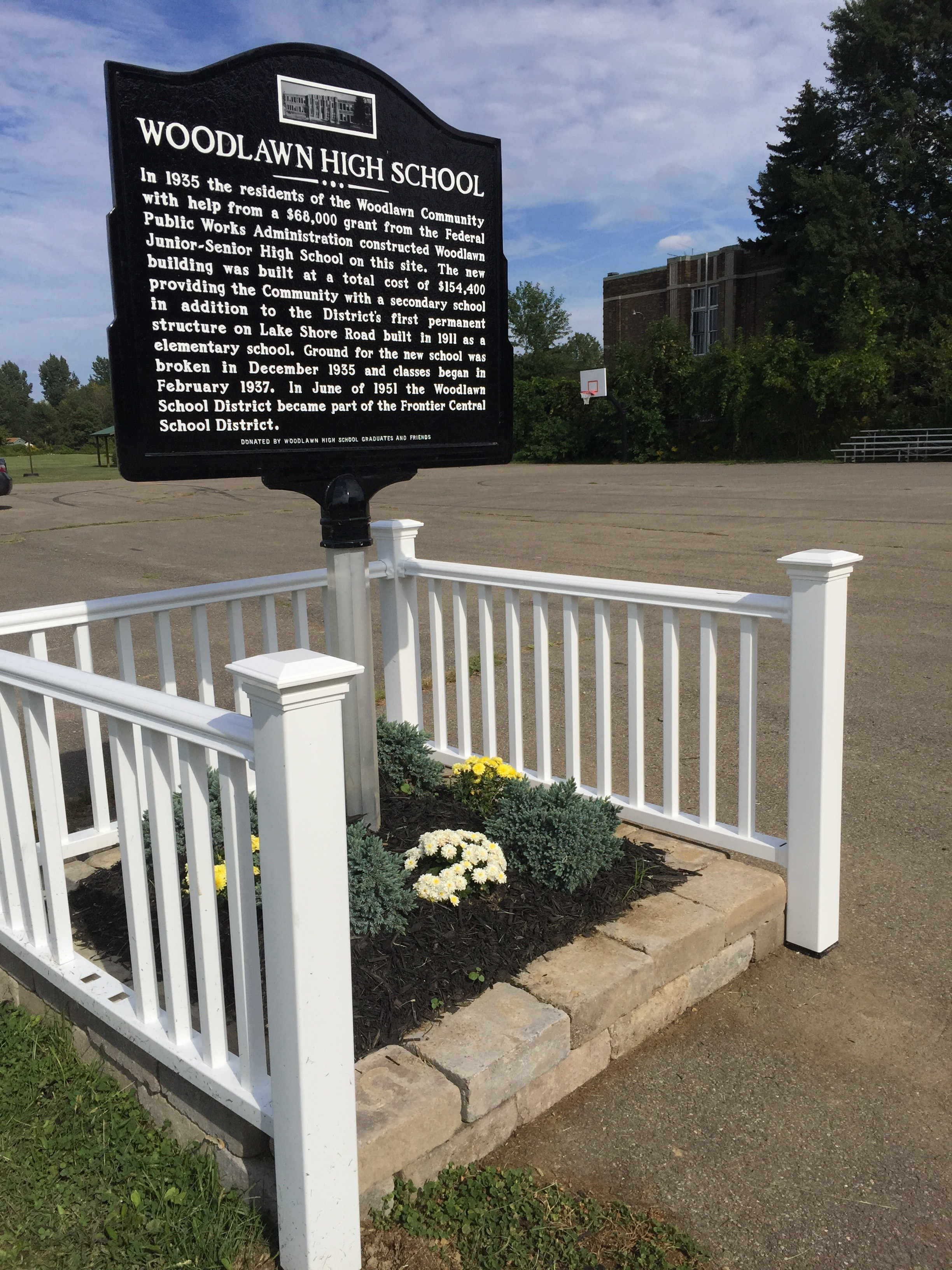 The former Woodlawn High School still stands in the background of the new historical marker.