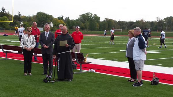 St. Francis High School President, Rev. Michael Sajda, offers a prayer during the blessing of the renovated football field Friday morning. University of Nevada head coach and St Francis alum Brian Polian, right, were among the 100 people in attendance. (Miguel Rodriguez / Buffalo News)