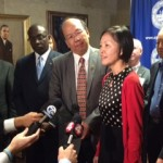 China's Yang Liqiong, speaks to reporters in Chinese, with Dr. Johnson Y.N. Lau, center, interpreting