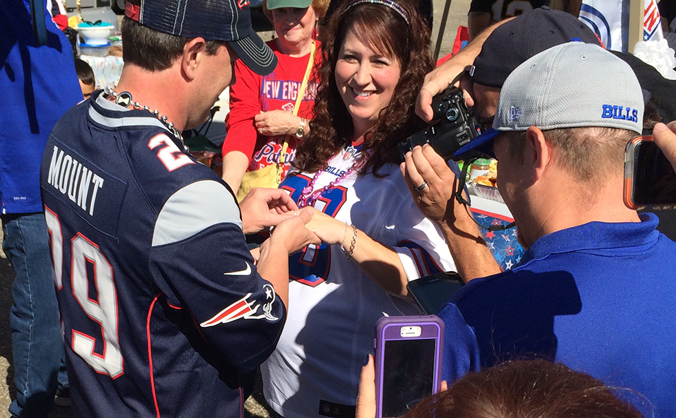 Rich Mount slides a wedding ring onto his wife Stacy's hand after the two were married in the parking lot before the Bills-Patriots game. (Nick Veronica/Special to the News)