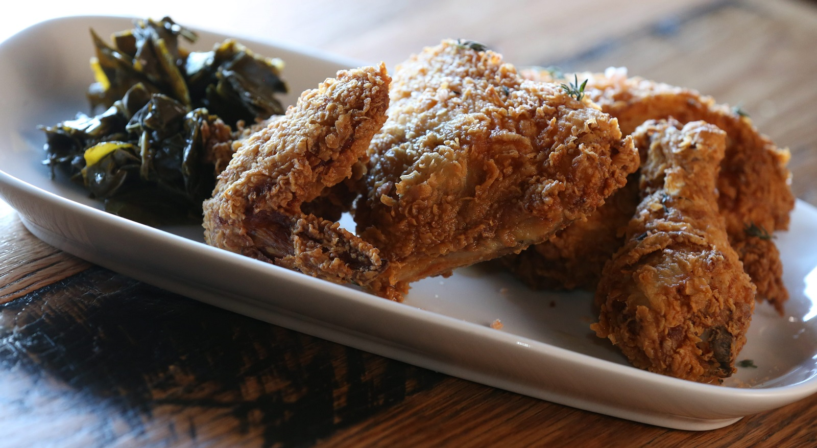 Toutant's buttermilk fried half-chicken comes with collard greens with cayenne sea salt. (Sharon Cantillon/Buffalo News file photoh)