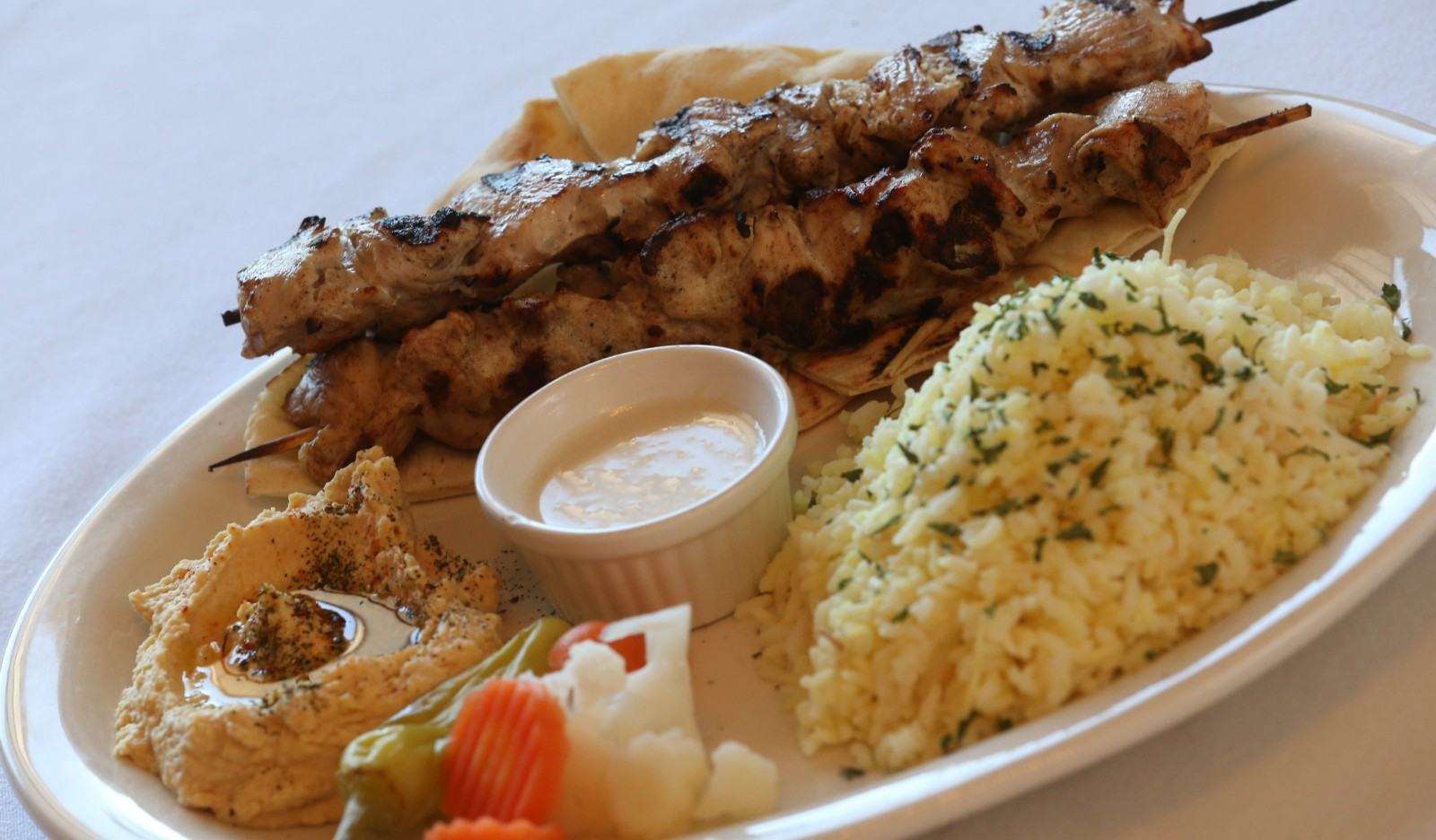 Grilled chicken kabob is served with pita, hummus, pickles and tahini sauce with choice of fries or rice. (Sharon Cantillon/Buffalo News)