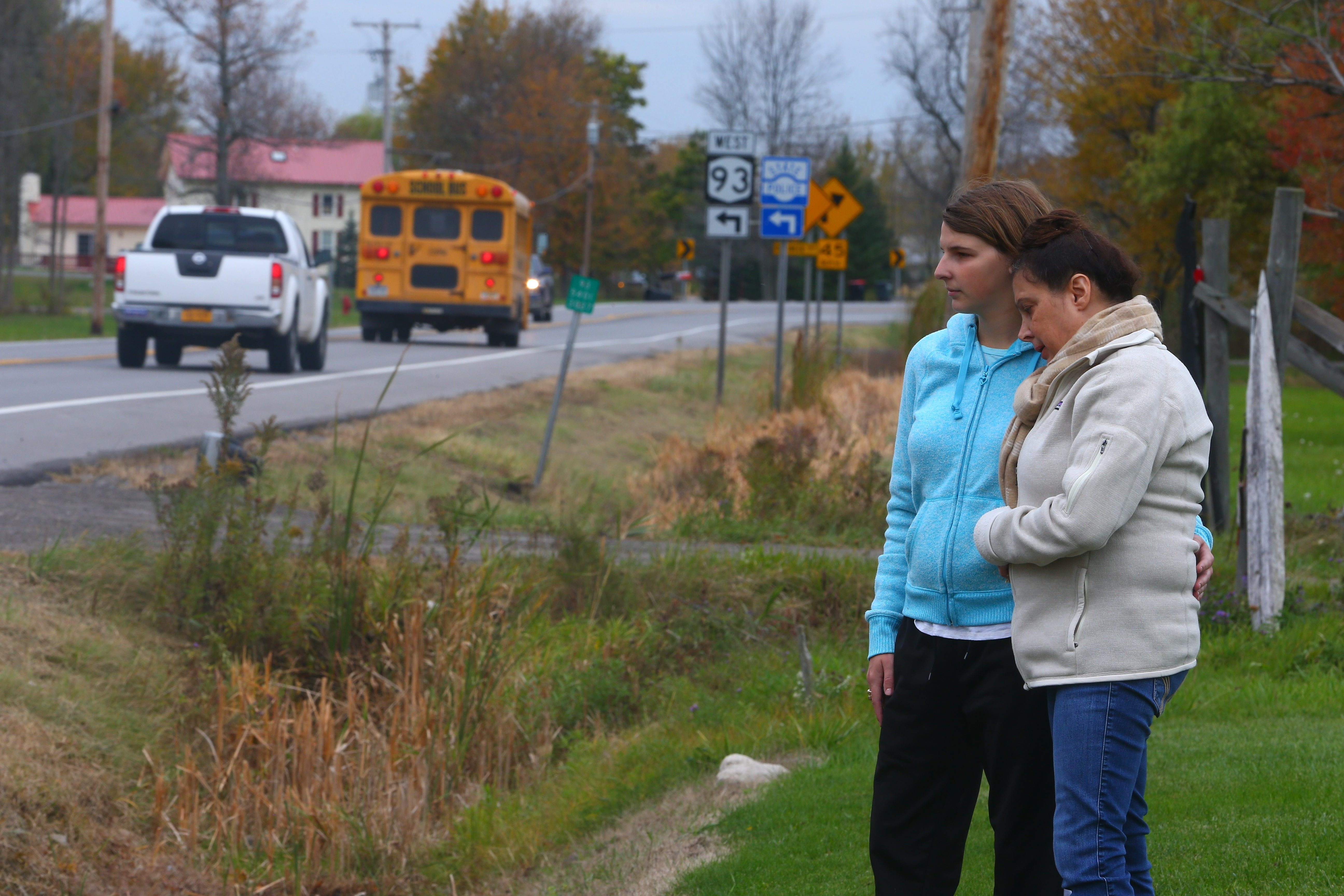Deborah Strassel, right, the widow of Robert Strassel, with her daughter Brittany, look at Route 93-Akron Road where Robert Strassel was killed Monday when he was hit by a car while cleaning up the remains of his dead dog, who had just been hit by another car in front of their home. (John Hickey/Buffalo News)