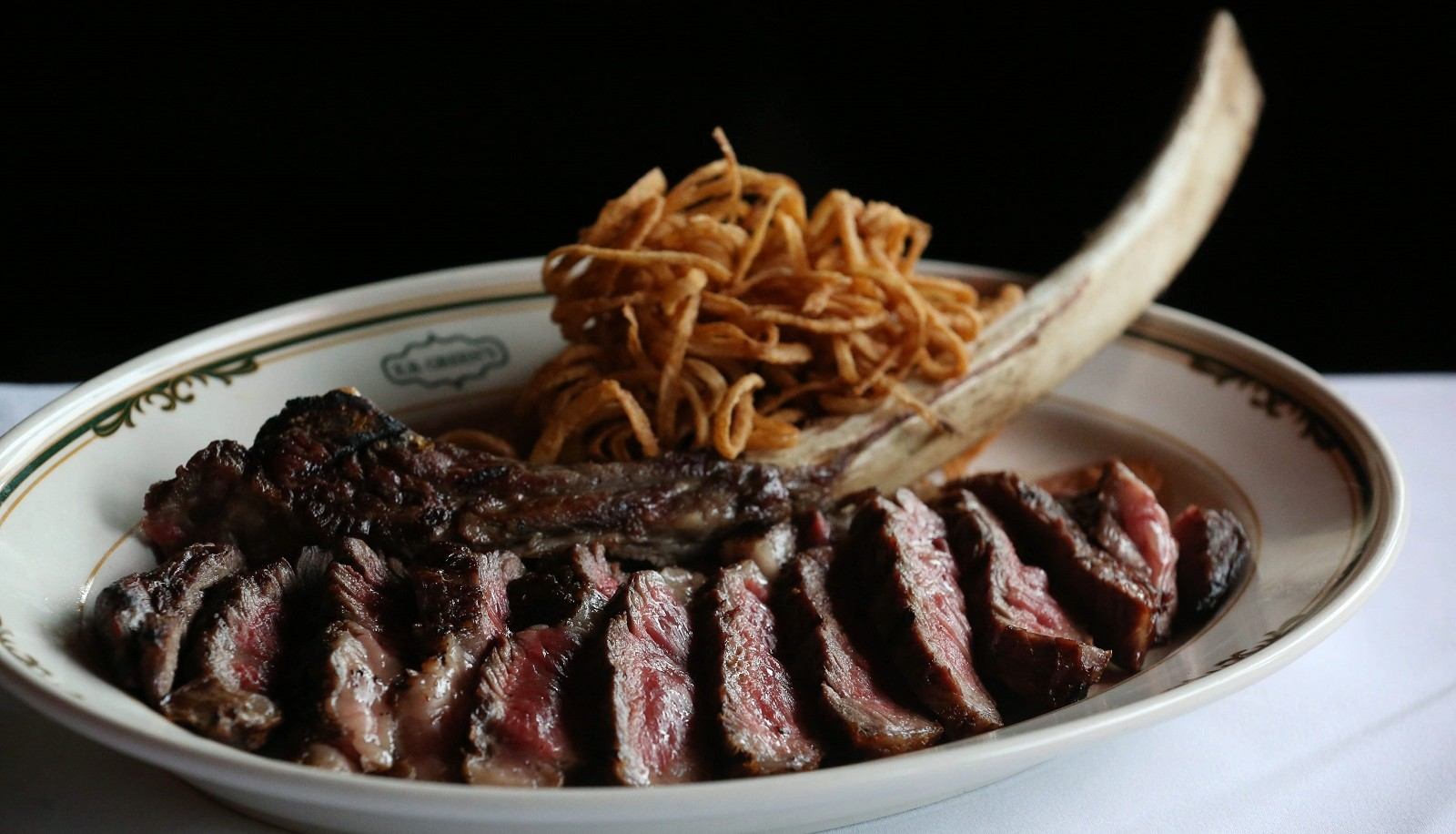 E.B. Green's Steakhouse's 30-ounce prime tomahawk ribeye comes with tobacco fried onions. (Sharon Cantillon/Buffalo News file photo)