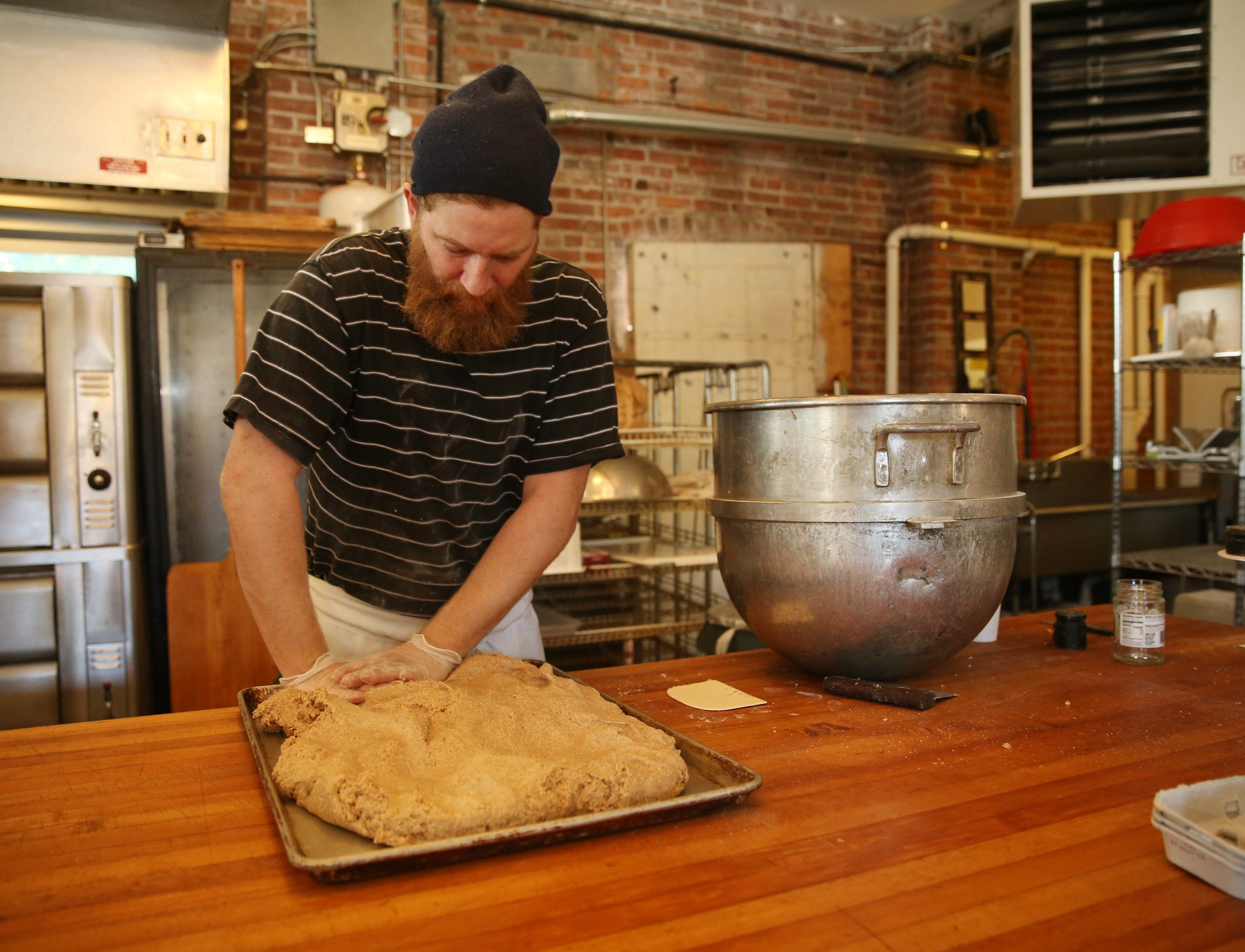Five Points owner Kevin Gardner spreads dough on a tray where it will sit for 24 hours to help break down phytic acid and enzymes and make it digestible for people with wheat sensitivities. See photo gallery at buffalonews.com.