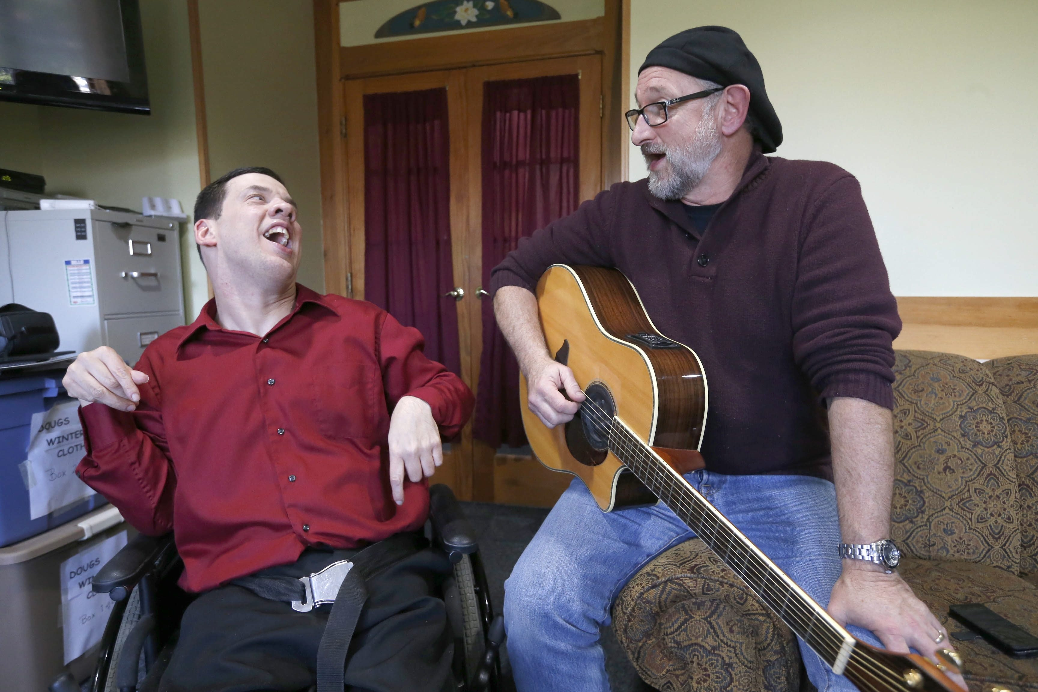 Accompanied by his life coach Gary Spears, right, Jason Smith, 46, left, sings a song he wrote for Stevie Wonder who will be performing Thursday in the First Niagara Center. (Robert Kirkham/Buffalo News)