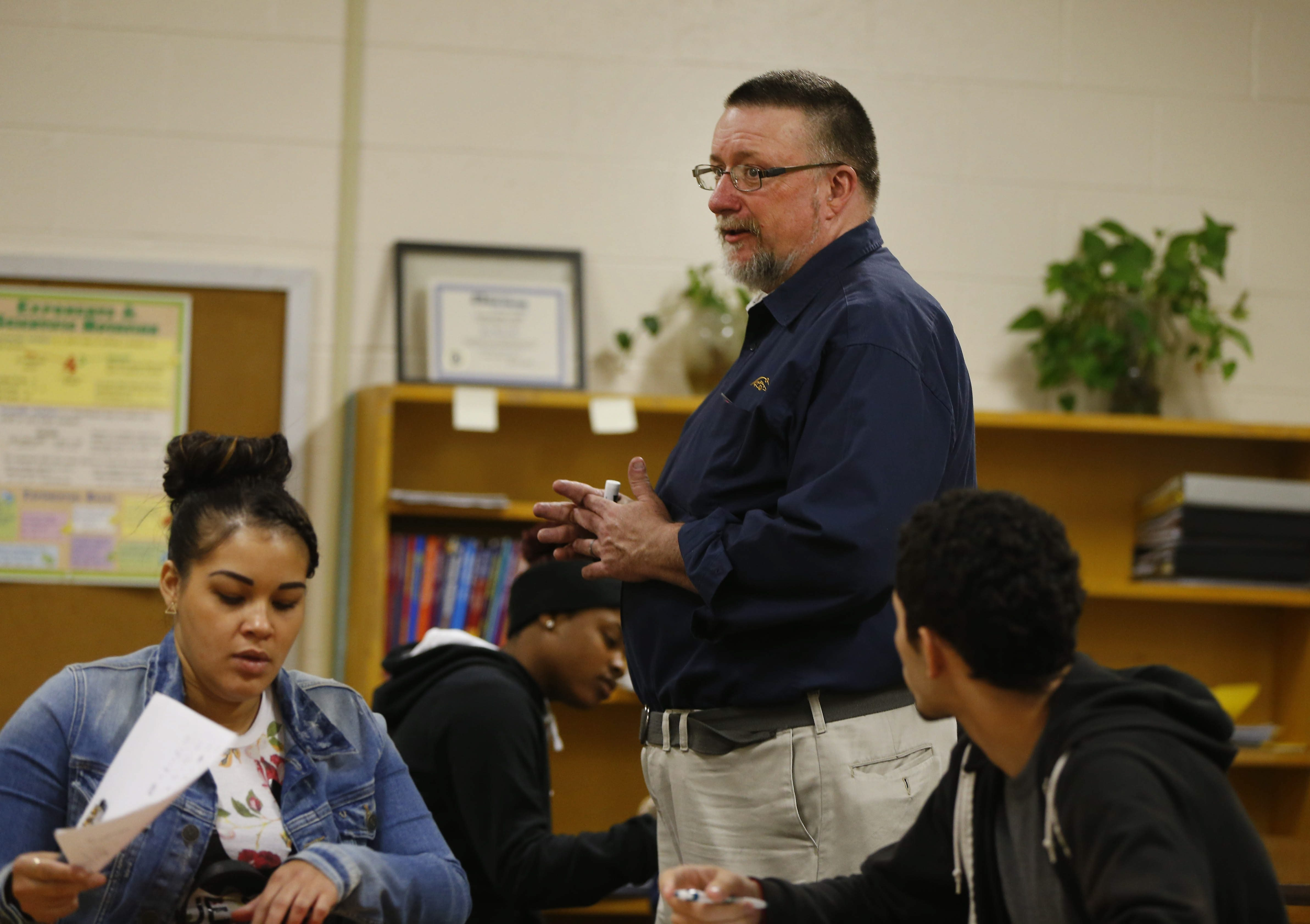 Instructor David Gorman works with students on math problems at the Career Collegiate Institute, the youth program of the Buffalo Public School's Adult Education Division.
