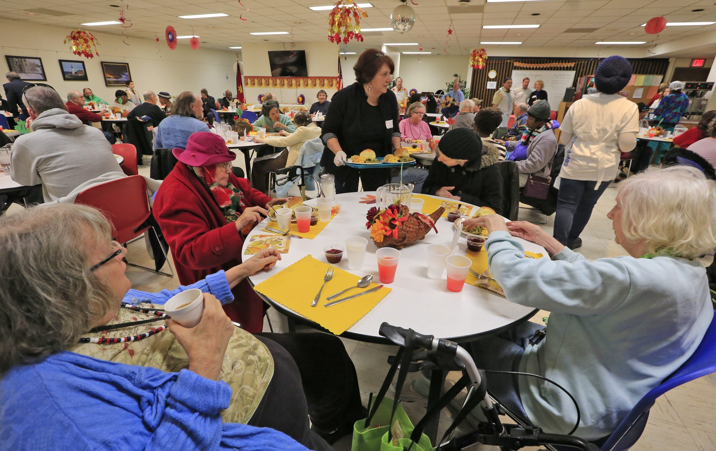 Cory Dussault, center, serves Thanksgiving dinner Thursday at the Salvation Army of Buffalo on Main Street. She and Mayor Byron W. Brown were among about 50 volunteers offering up food and fellowship to guests ranging from homeless people to families and senior citizens.