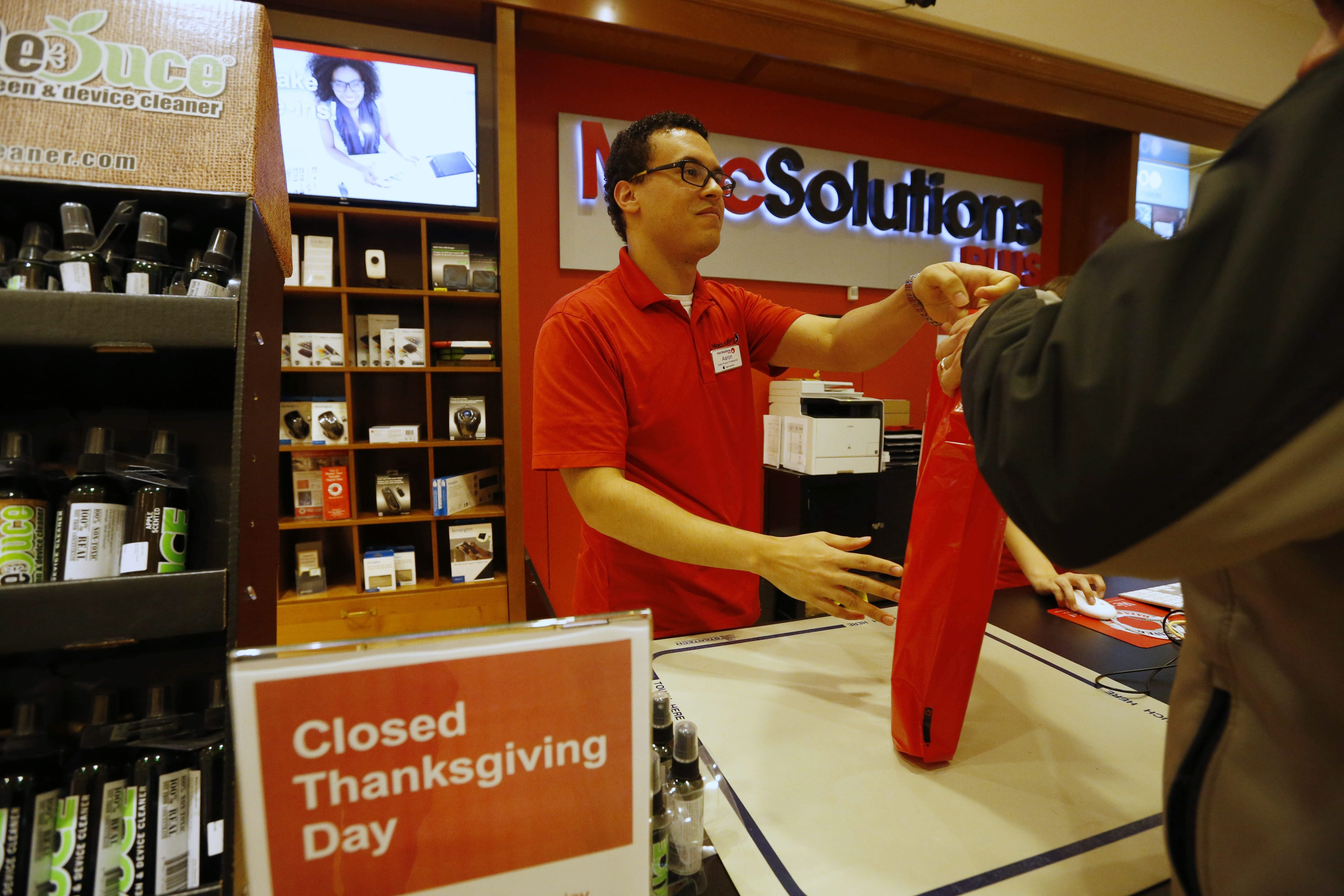 Aaron Miller sells a laptop to a customer at the MacSolutions Plus store at the Eastern Hills Mall, Tuesday, Nov. 24, 2015.  The store will be closed on Thanksgiving Day to let employees spend time with family.  (Derek Gee/Buffalo News)