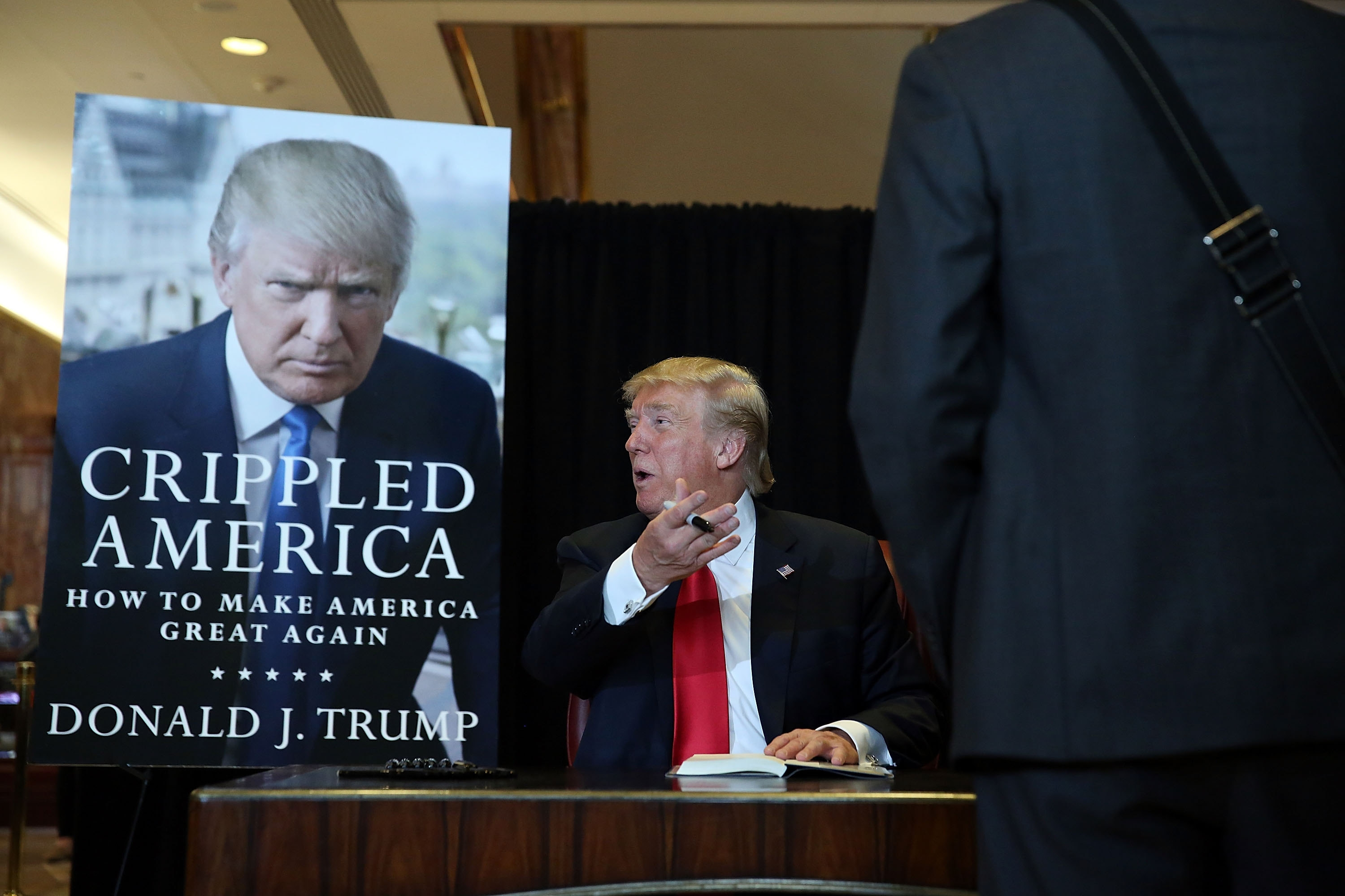"Republican presidential candidate Donald Trump signs his new book, ""Crippled America: How to Make America Great Again,"" at the Trump Tower Atrium on Nov. 3 in New York City. Trump has made an art of turning campaign rallies into fact-free zones, Rod Watson says. (Getty Images)"