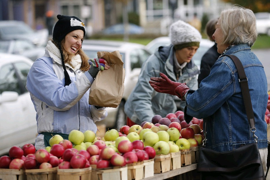 A customer buys apples at the Tom Tower Farm stand at the Elmwood-Bidwell Farmers Market, which will continue indoors from Dec. 5 to April 30 in Buckham Hall on the SUNY Buffalo State campus. (Derek Gee/Buffalo News)
