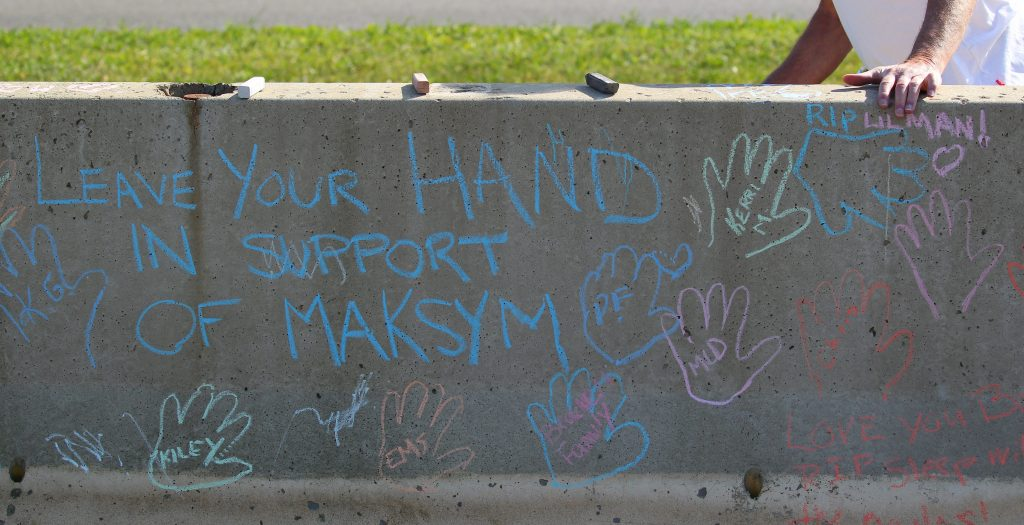 People write on the concrete barrier in Delaware Park before the vigil Tuesday, June 2, 2015. (Mark Mulville/Buffalo News)