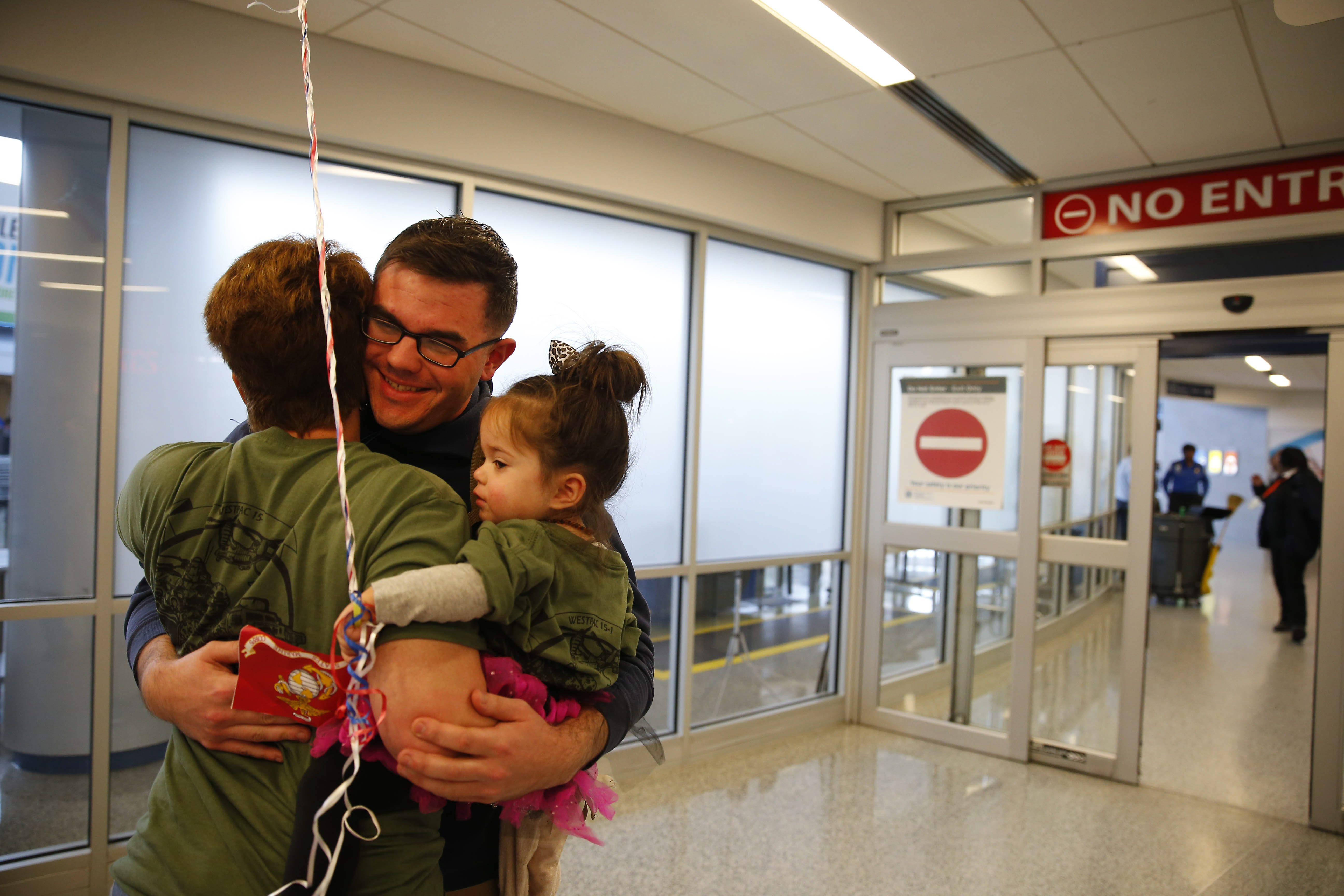 Marine Corporal Alex Hall is greeted after taking a red-eye flight by his mom Lisa Hall and niece Diem Garro at the Buffalo Niagara International Airport in Cheektowaga Wednesday, December 23, 2015. (Mark Mulville/Buffalo News)