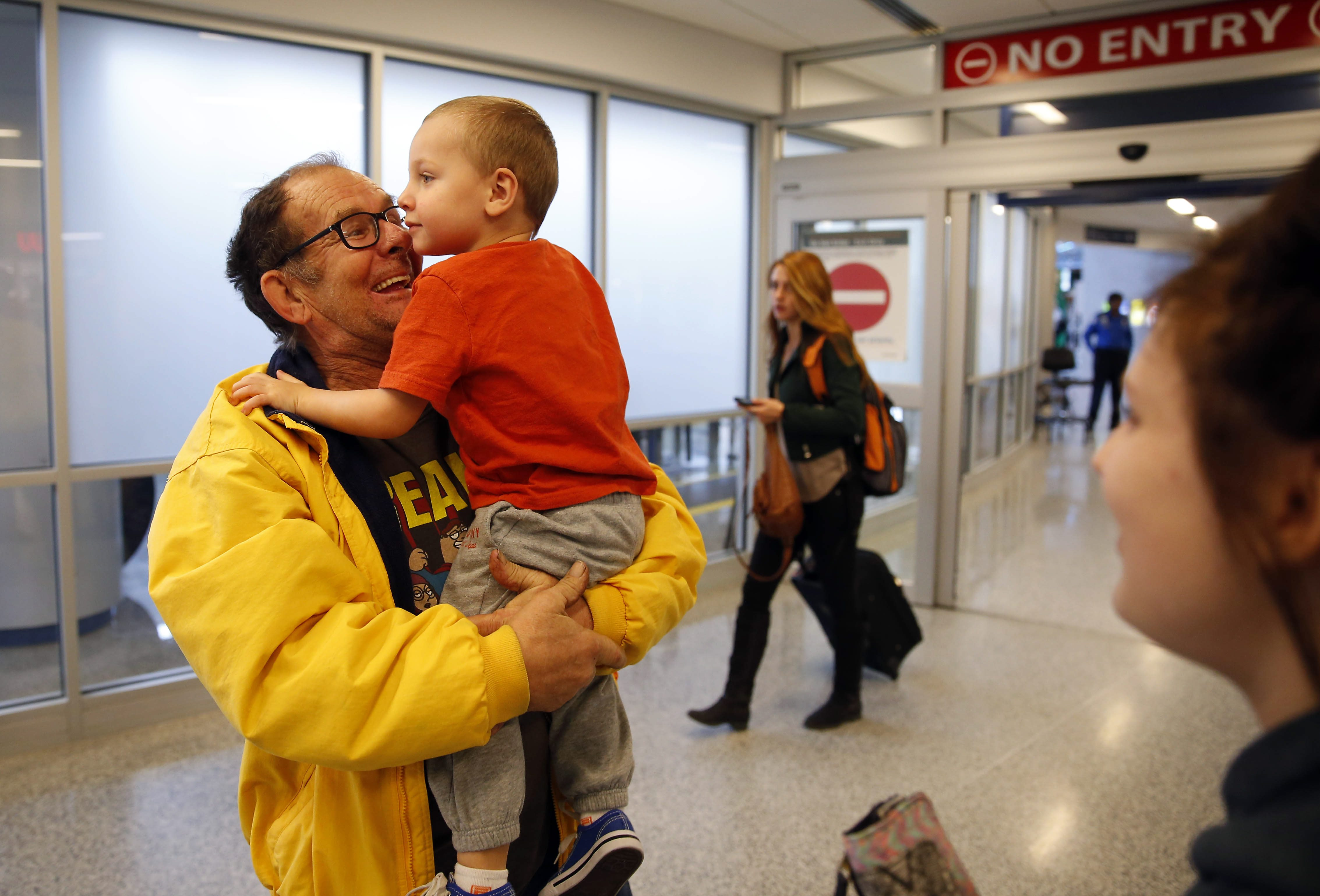 Ed Rak of Dunkirk, greets his grandson Landon LaFaur of Texas, at the airport on Dec. 23. (Mark Mulville/Buffalo News)