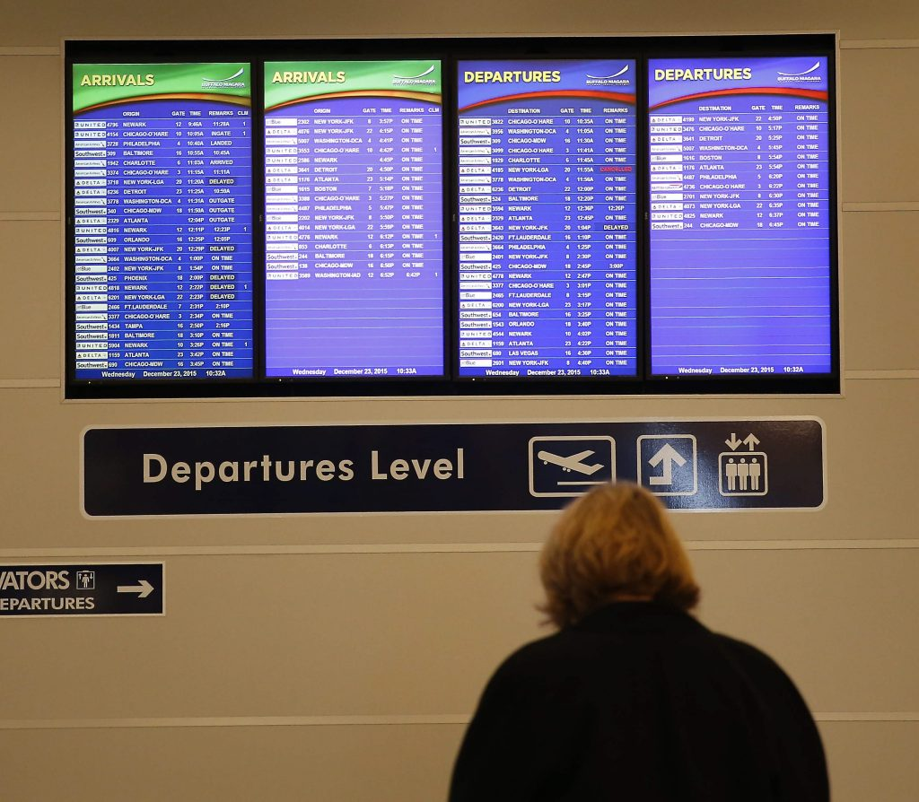 A traveler checks the arrivals at the airport on Dec. 23. (Mark Mulville/Buffalo News)
