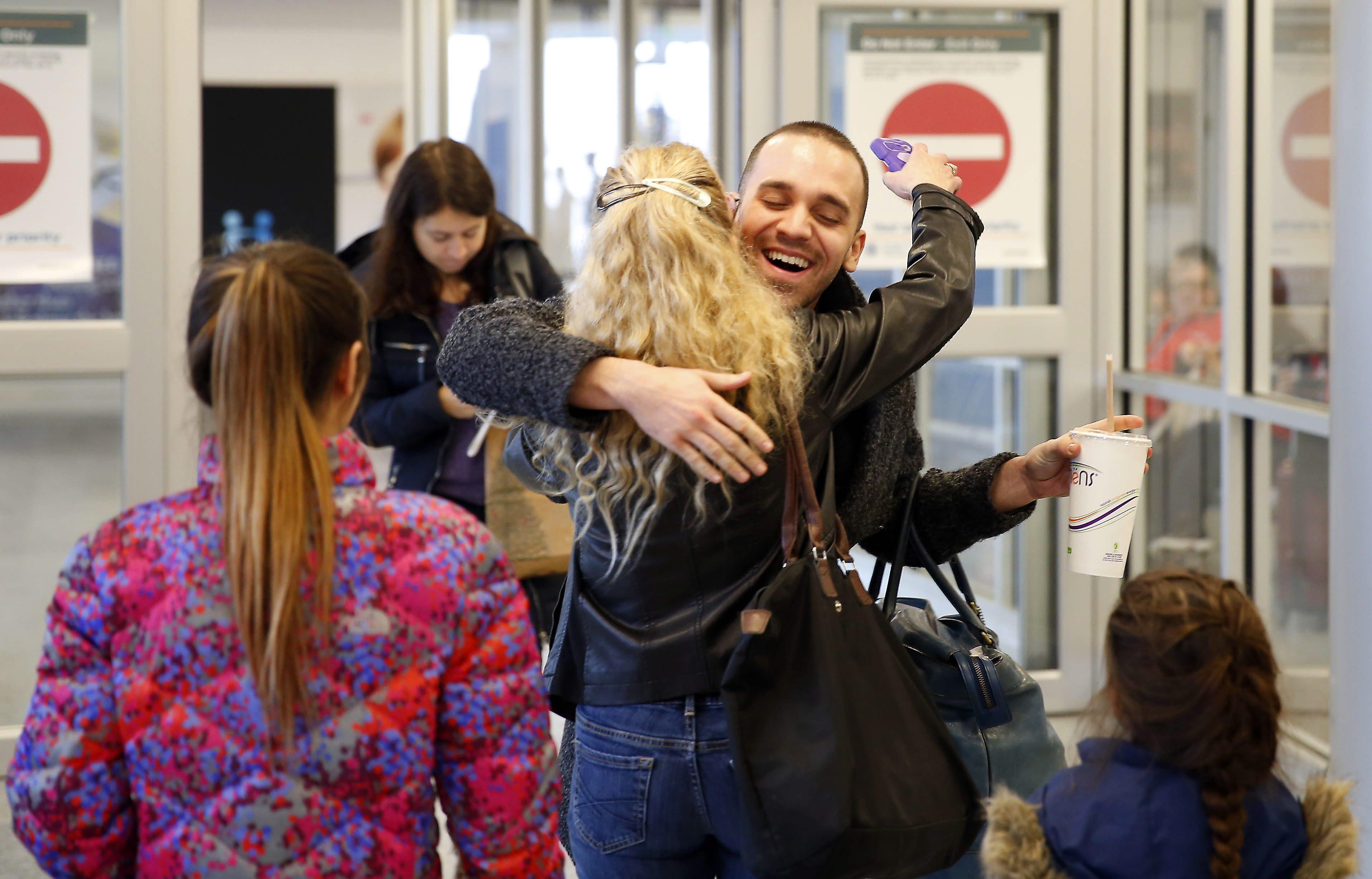 Deon Oliverio gets a hug from his mother, Lauretta Hersch, as he arrives at the Buffalo Niagara International Airport on Dec. 23.  (Mark Mulville/Buffalo News)