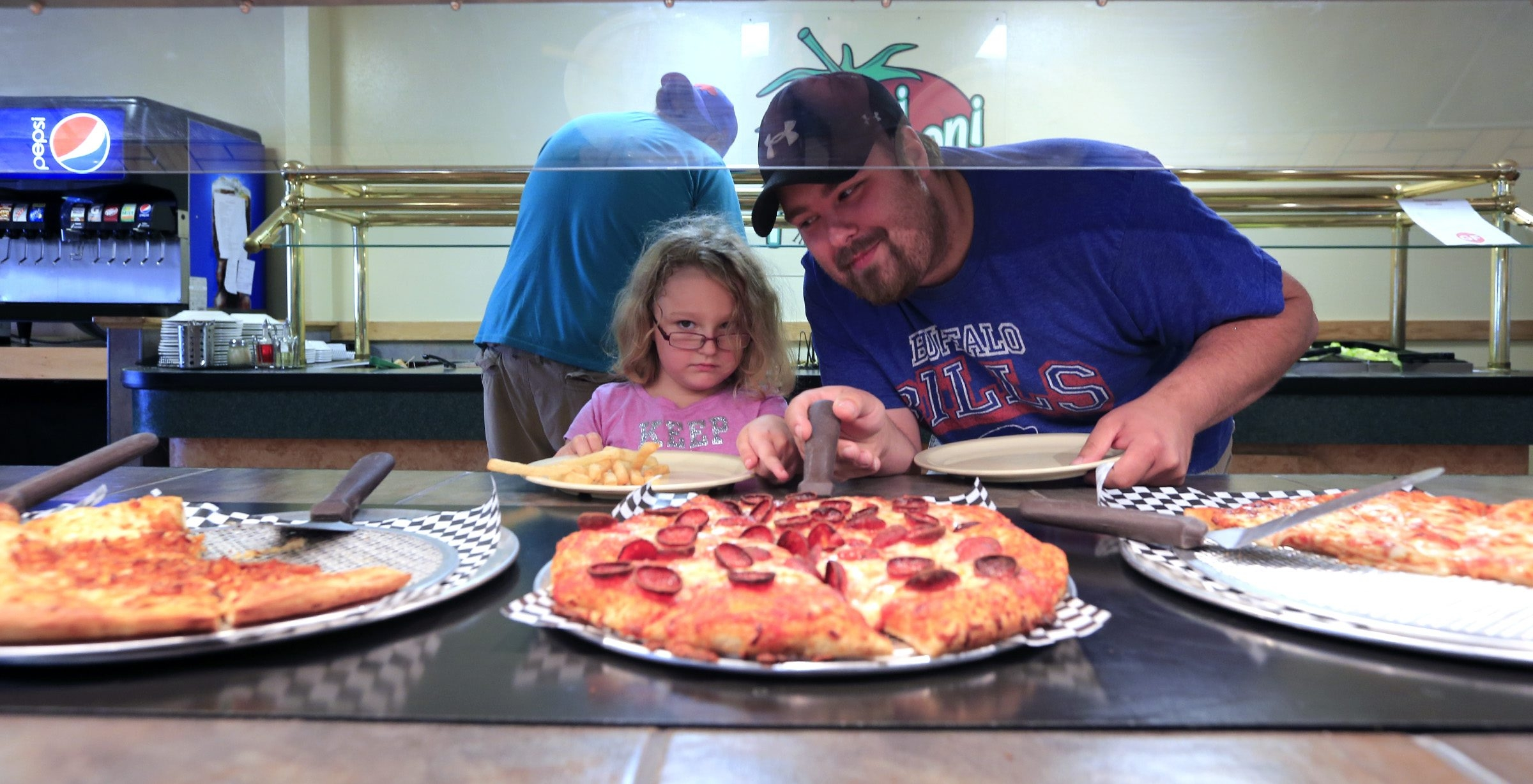 Jerry Jarmusz and his daughter Kylie pick out a pizza at Toni Pepperoni's buffet in Orchard Park.