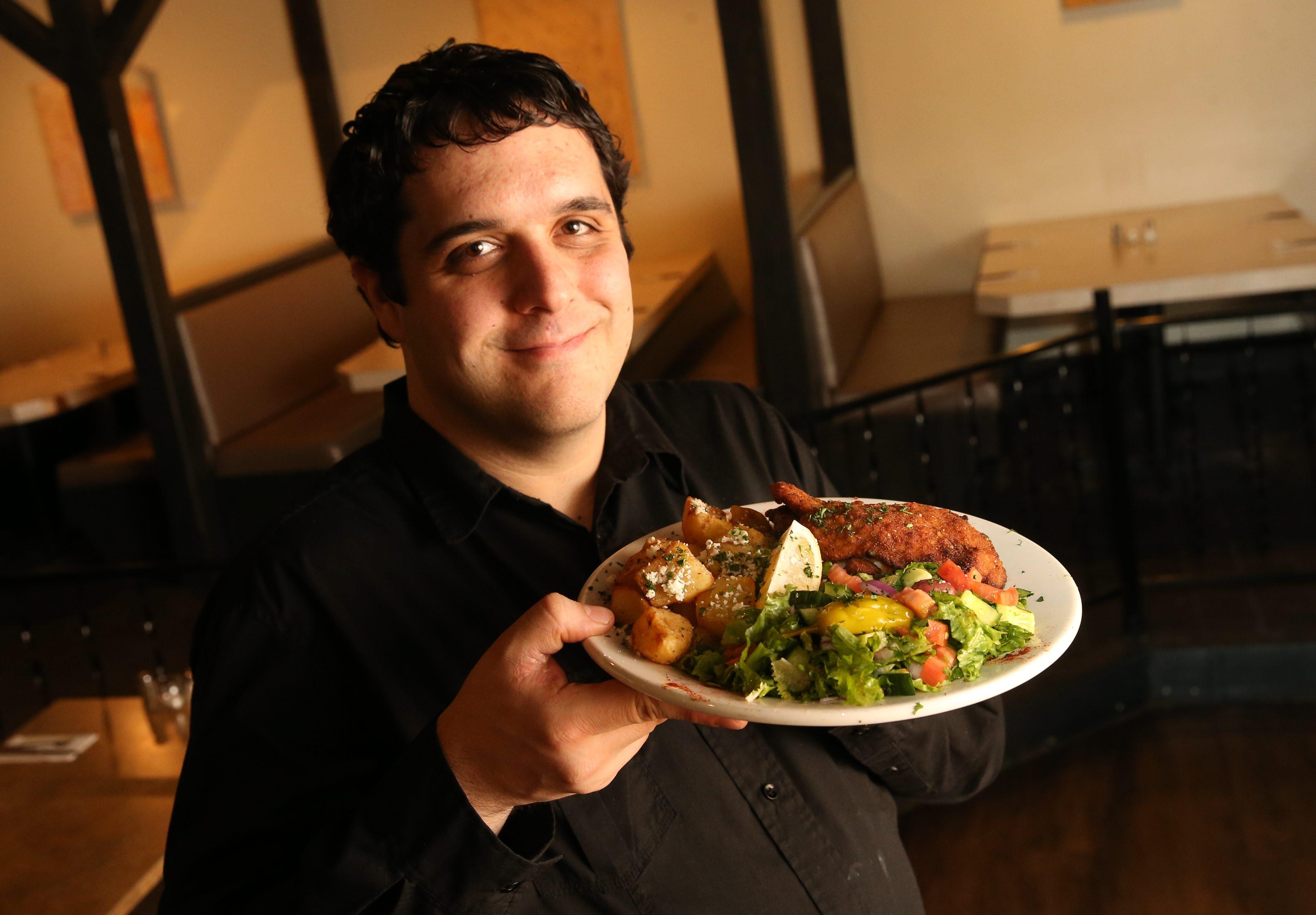 Server Leonardo Giangreco Jr. presents the chicken schnitzel at the Falafel Bar. (Sharon Cantillon/Buffalo News)