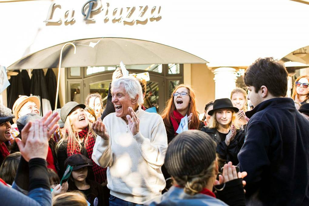 """Dick Van Dyke joins the flash mob that gathered in a Southern California shopping center in celebration of his 90th birthday for a rendition of """"Let's Go Fly a Kite."""" The event was led by Lancaster's Dena and Jenna Spellman. (Nicola Buck)"""