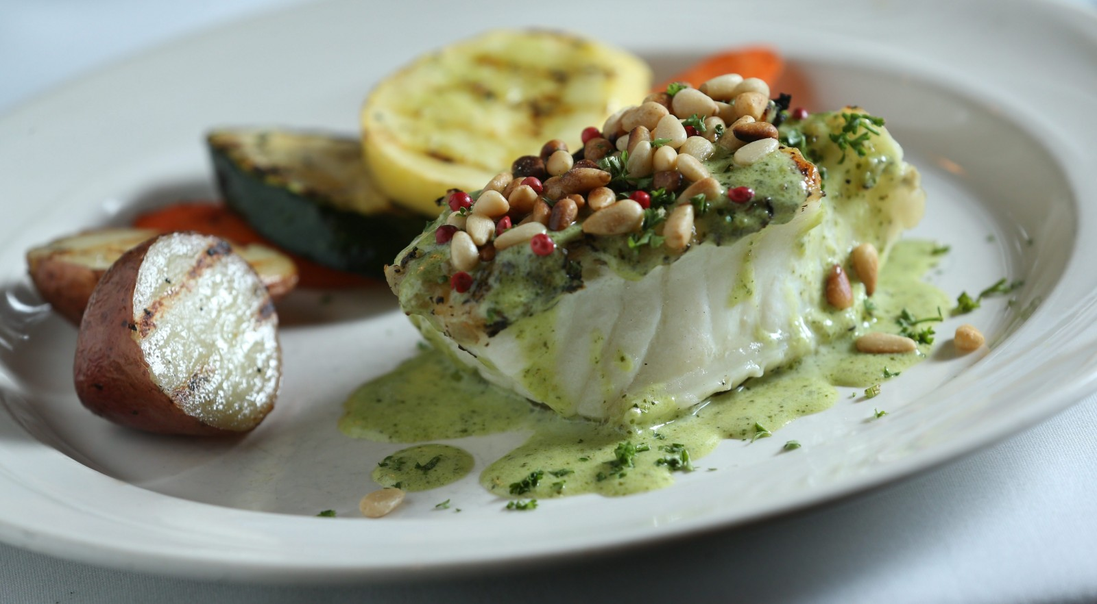 San Marco's sea bass is pan-seared with white wine, lemon and herbs, finished on the grill and topped with a creamy pesto sauce. (Sharon Cantillon/Buffalo News)