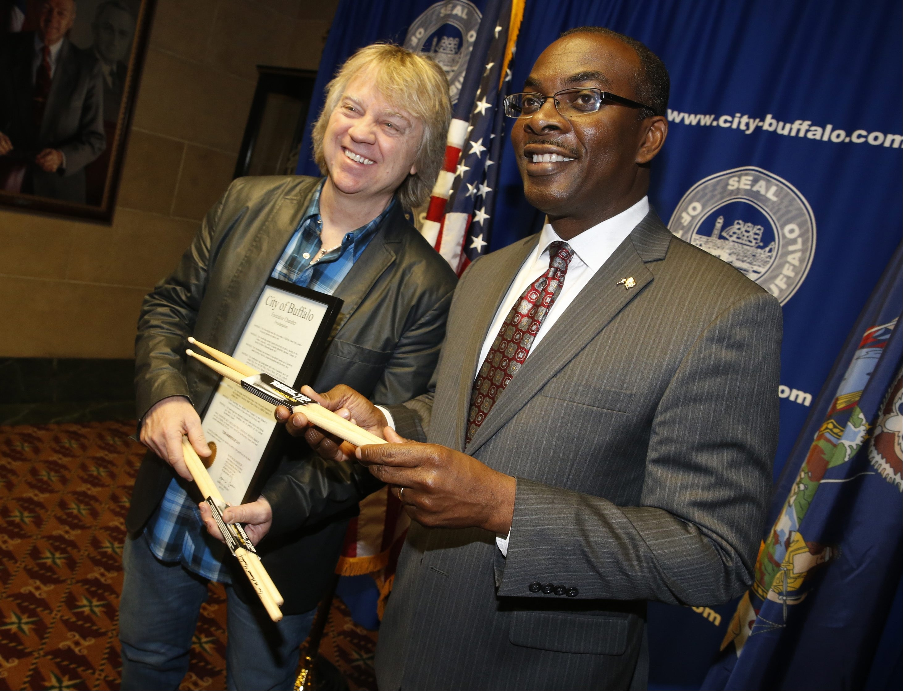 "Grammy award winning musician Tom Hambridge, left, visits City Hall as Buffalo Mayor Byron Brown declared ""Tom Hambridge Day"" on Monday, Dec. 28, 2015.   They are holding signed drum sticks."