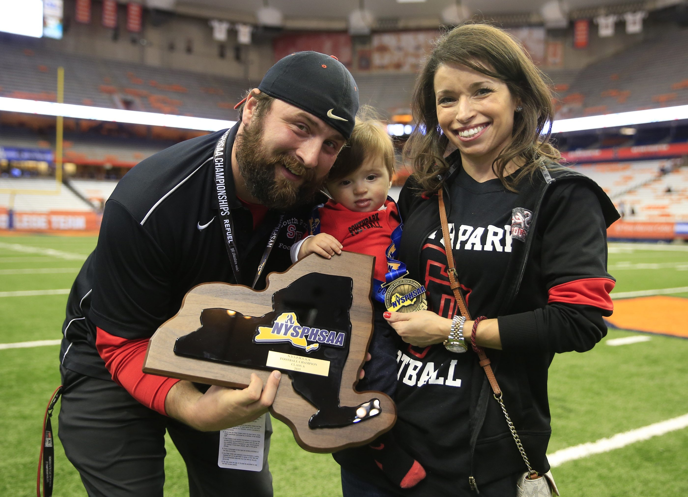 South Park coach Tim Delaney celebrates with his wife and son after defeating Our Lady of Lourdes for the New York State Class A championship  at the Carrier Dome.