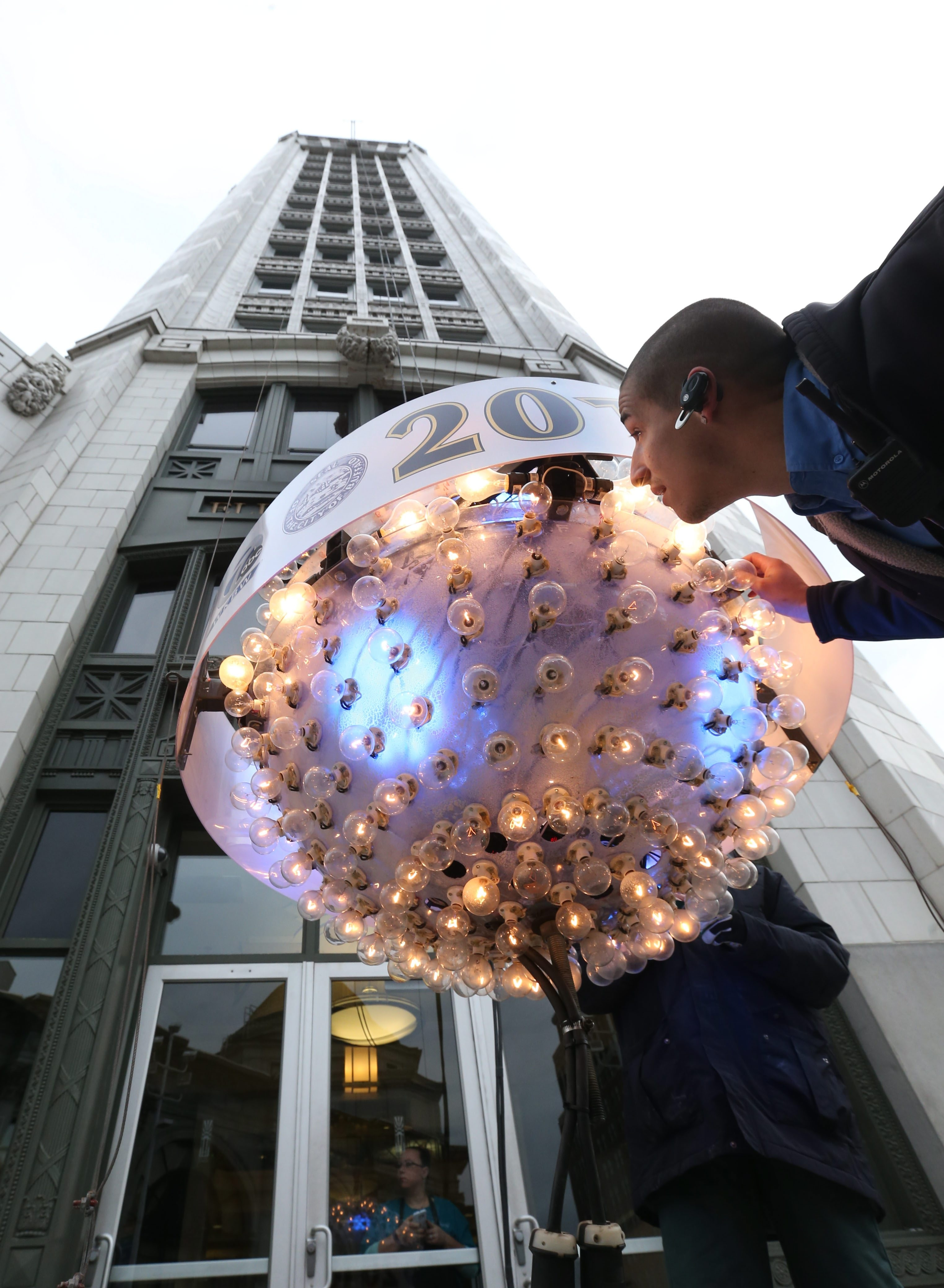 Iskalo Development worker Robert Torres replaces bulbs before a test run of the ball drop at the Electric Tower.