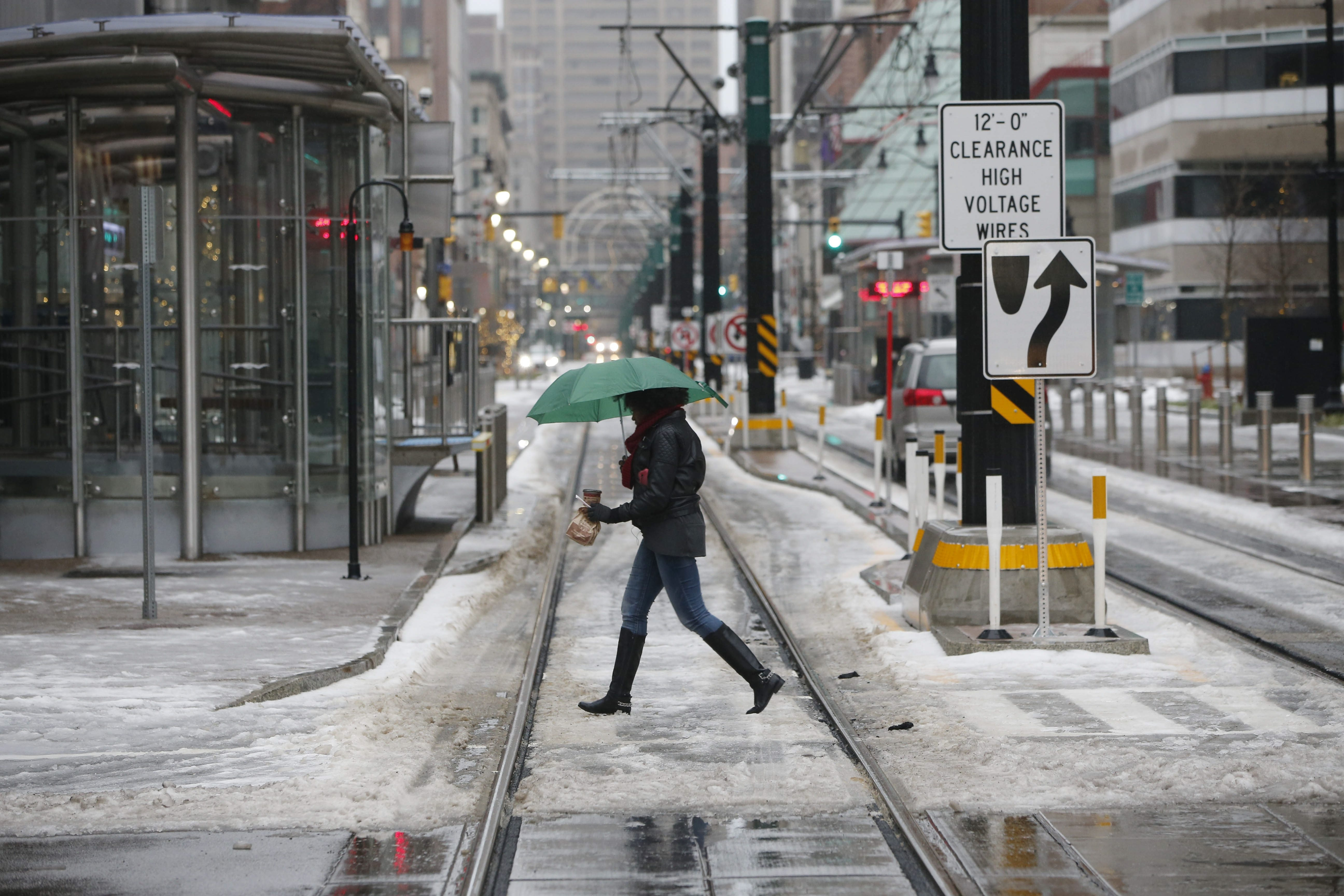 A woman with the morning essentials – an umbrella and a hot drink – crosses Main Street while walking down Chippewa, where a heavy layer of slush and ice remained from overnight snow and freezing rain on Tuesday.