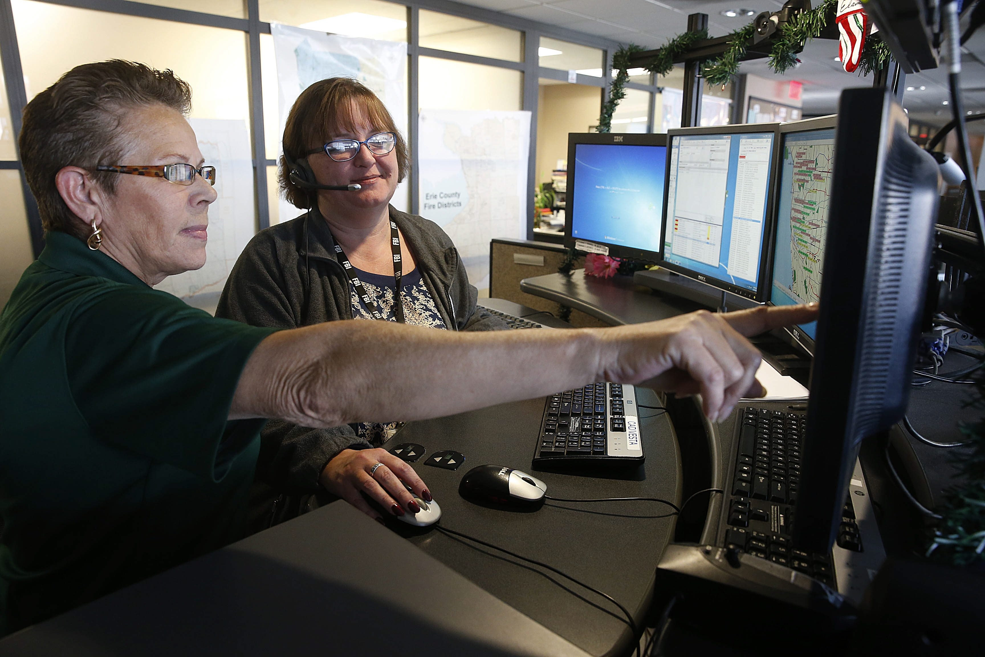 Lisa Sears, right, an eight-year 911 operator, works at her station at Central Police Services in the Public Safety building in Buffalo on Dec. 8. She often uses the expertise of 35-year veteran Judy Torres, left, when she gets an emergency call in Spanish.