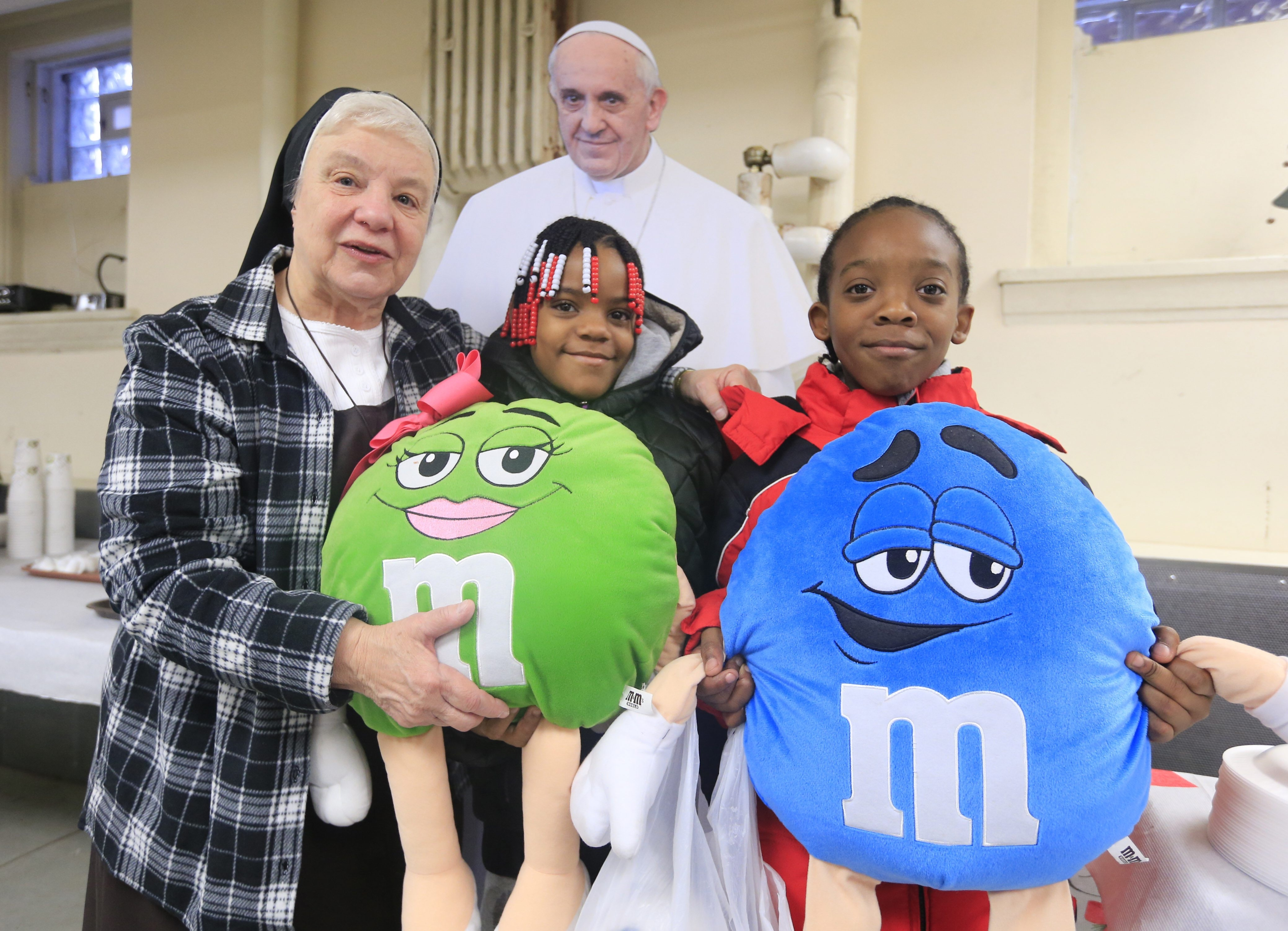 Sister Mary Johnice Rzadkiewicz poses with Speshalle and Antoine Chaney in front of a life-size cutout of Pope Francis, after the children received gifts during the annual Christmas dinner at the Response to Love Center on Friday.