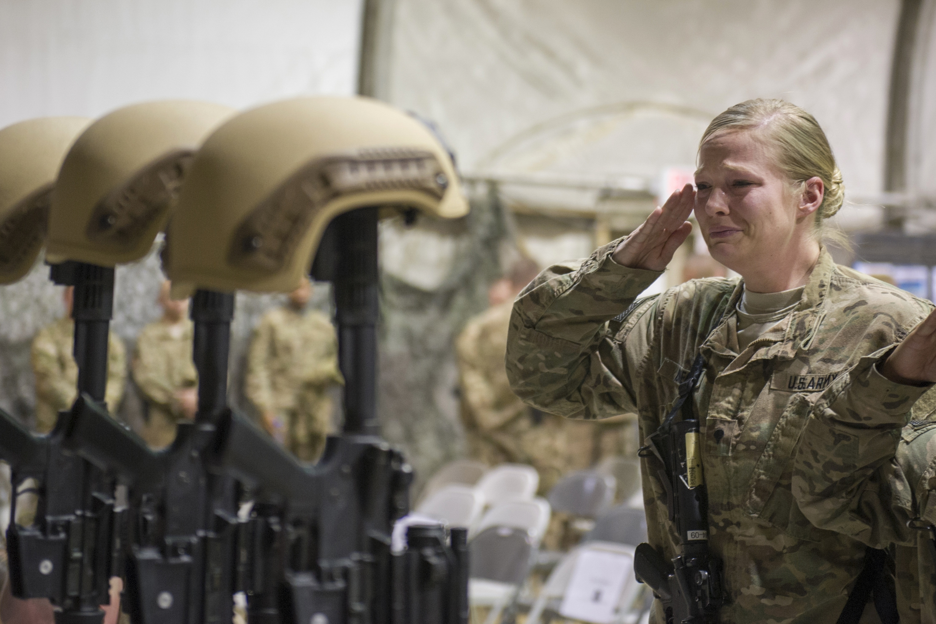 A U.S. Army soldier salutes during a memorial ceremony at Bagram Airfield in Afghanistan for the six Air Force members killed in a suicide attack Monday. (New York Times)