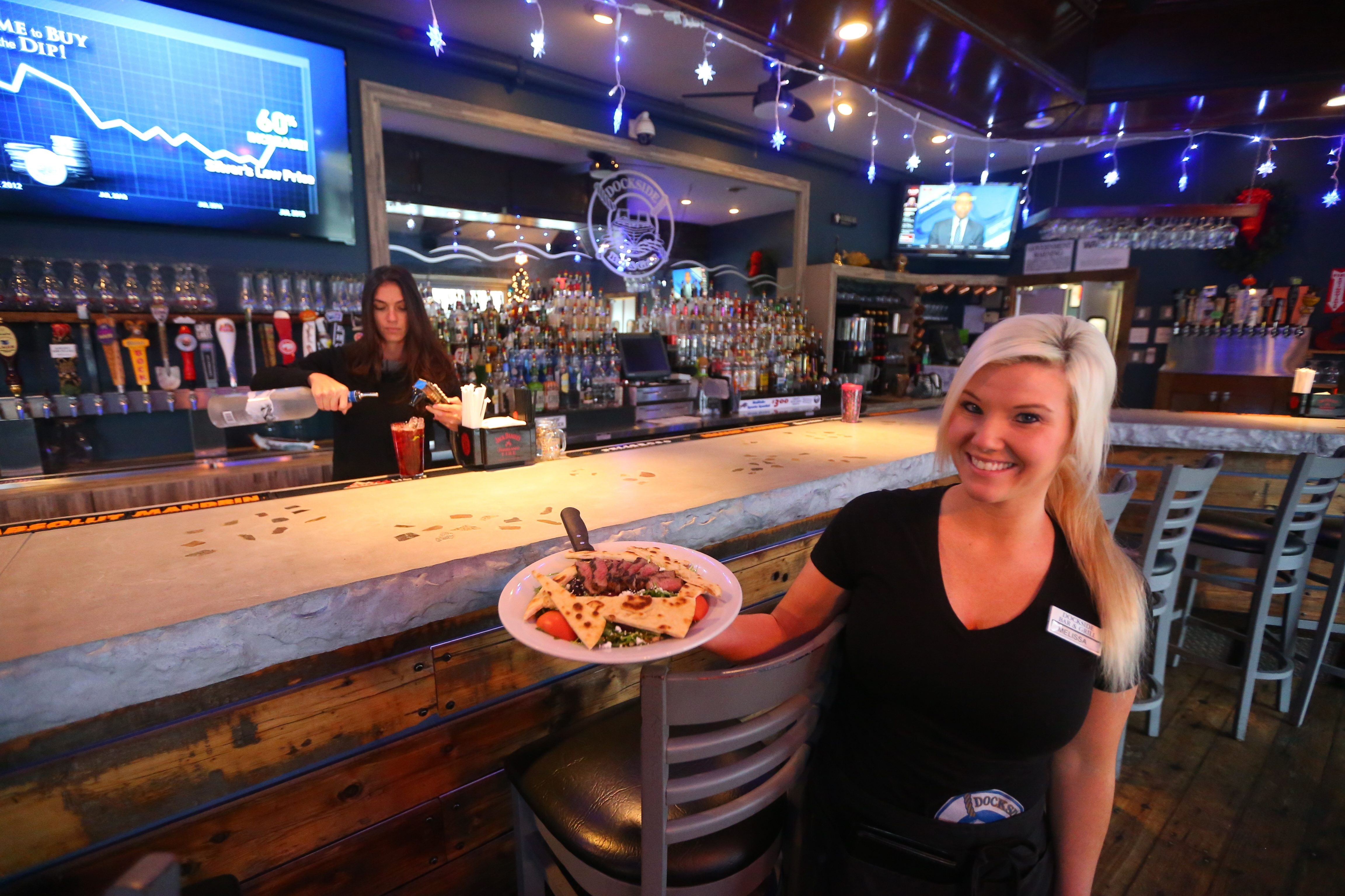 Dockside Bar & Grill server Melissa Meyer, right, presents a Steak & Arugula salad as shift manager Alana Turchiarelli mixes a drink in the renovated – and now open year-round – North Tonawanda restaurant.