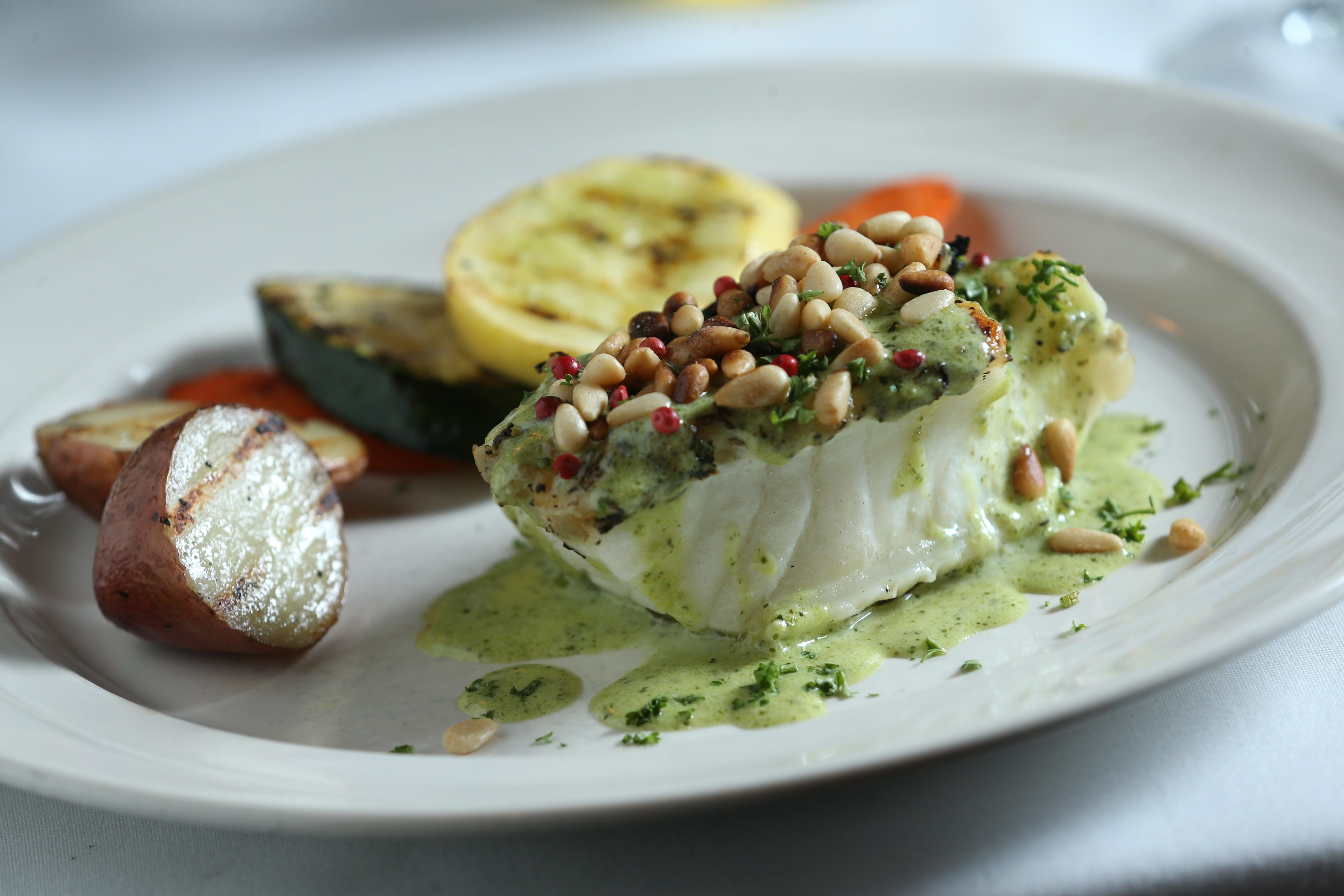 Fish filet is pan-seared with white wine, lemon and herbs, finished on the grill and topped with a creamy pesto sauce.