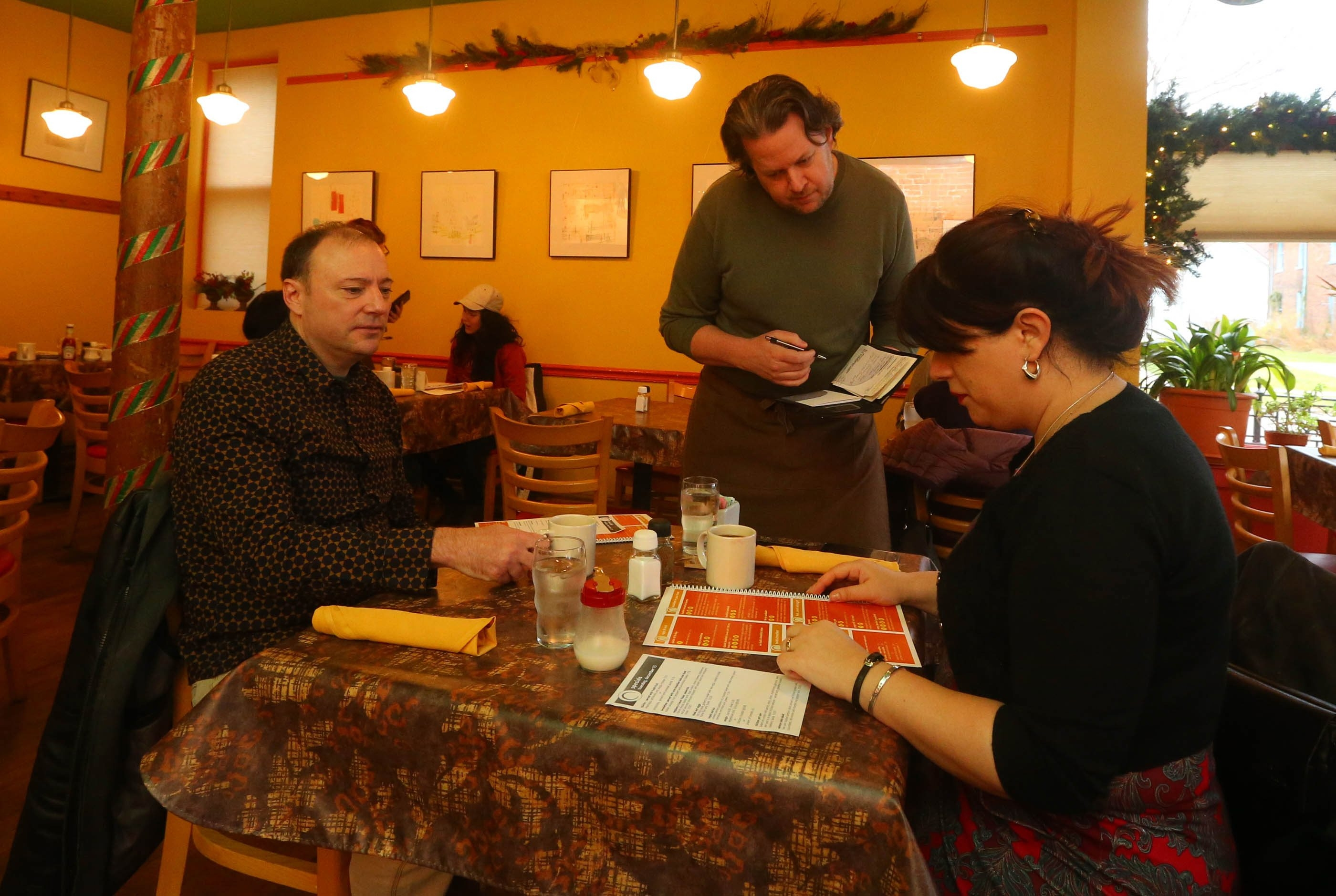 """Ted Gates, a server at Betty's on Virginia Street in Buffalo, waits on Ed and Eka Pudlo, visitors from Chicago. Because of higher wage costs, a co-owner says, the restaurant is """"trying to figure out how we can survive"""" while being fair to both staff members and customers."""