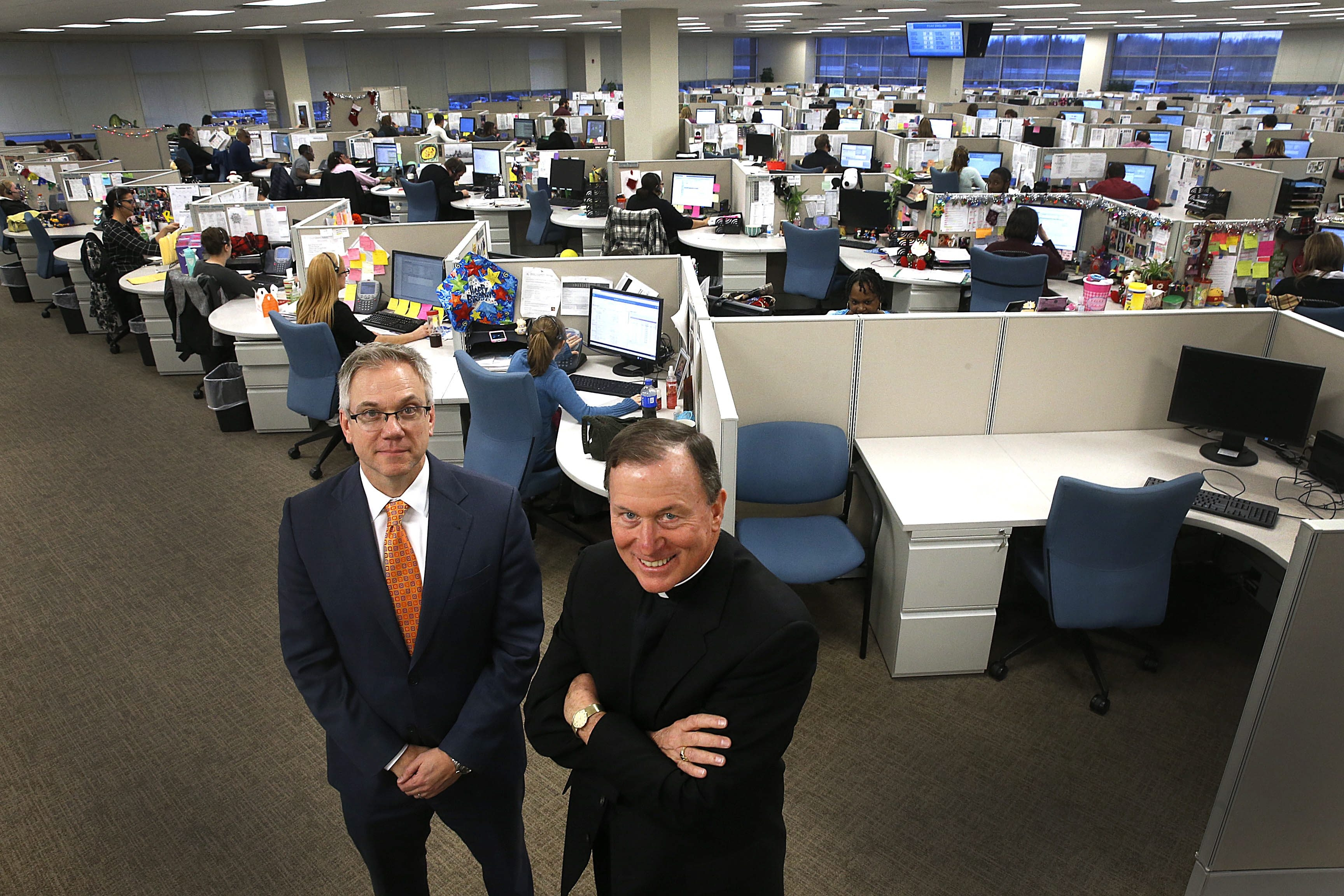 The Rev. Patrick J. Frawley, right,  president and CEO of Fidelis Care, and David Thomas, executive vice president and COO, show off the health insurer's expansion at its Getzville offices. (Robert Kirkham/Buffalo News)